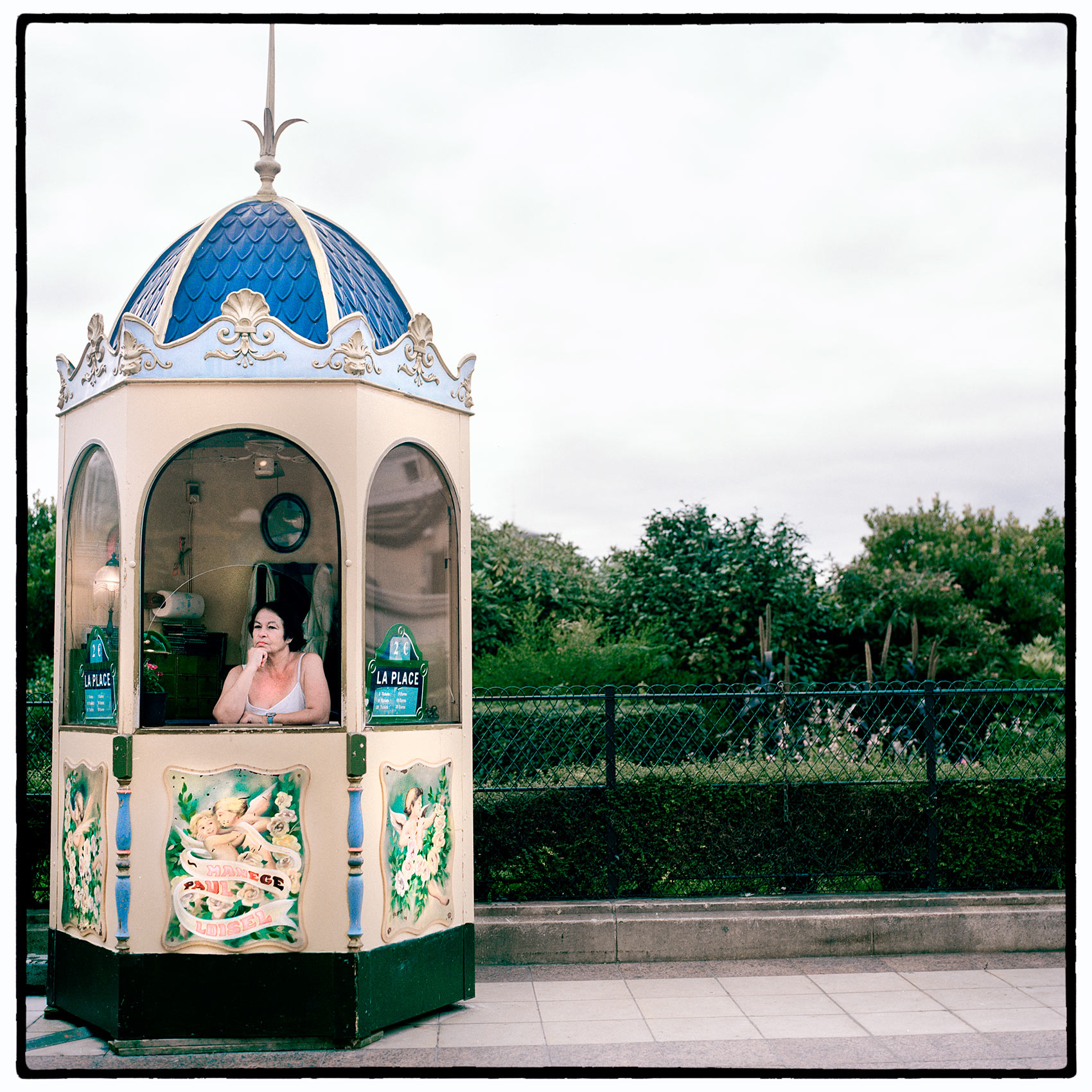 a-ticket-taker-waits-inside-her-booth-outiside-a-fairground-in-paris-france