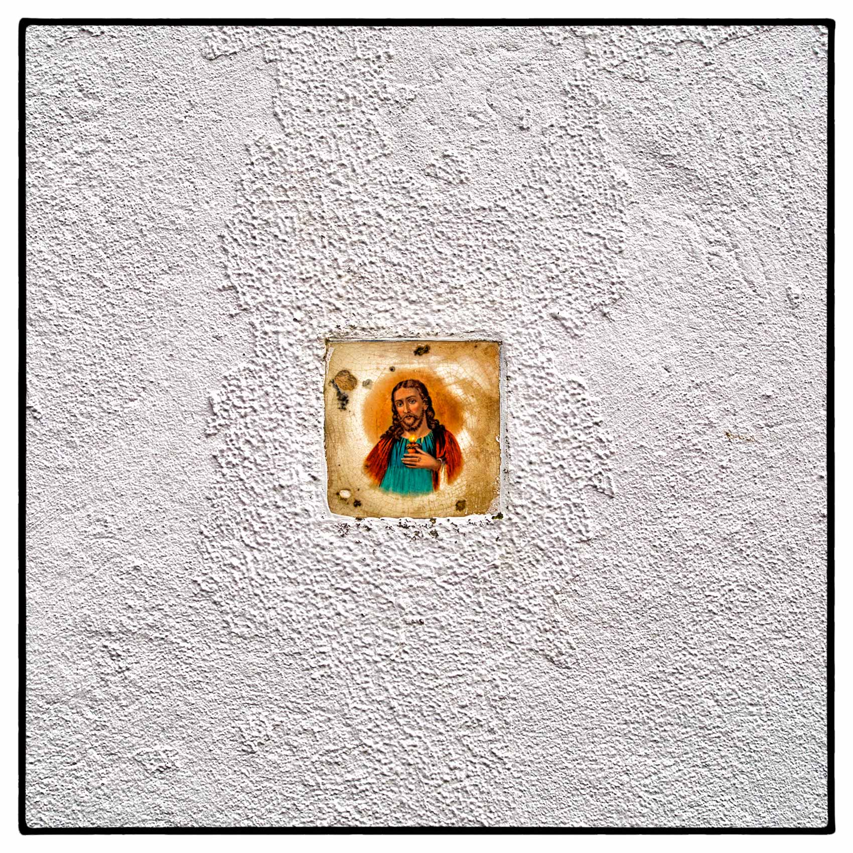 a-tile-with-the-face-of-jesus-christ-on-it-placed-in-a-wall-outside-a-home-in-portugal