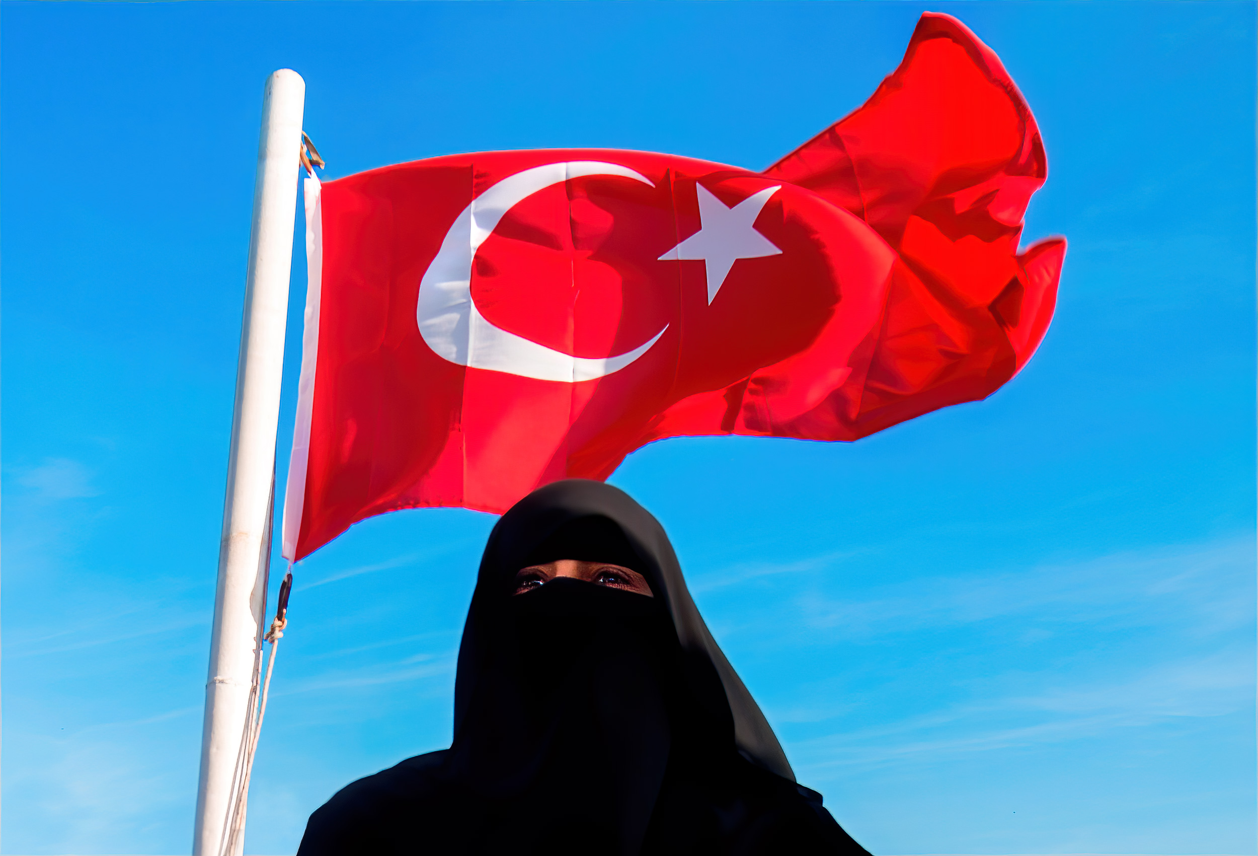a-turkish-flag-flies-behind-a-woman-wearing-a-burqa-on-a-tour-boat-in-istanbul