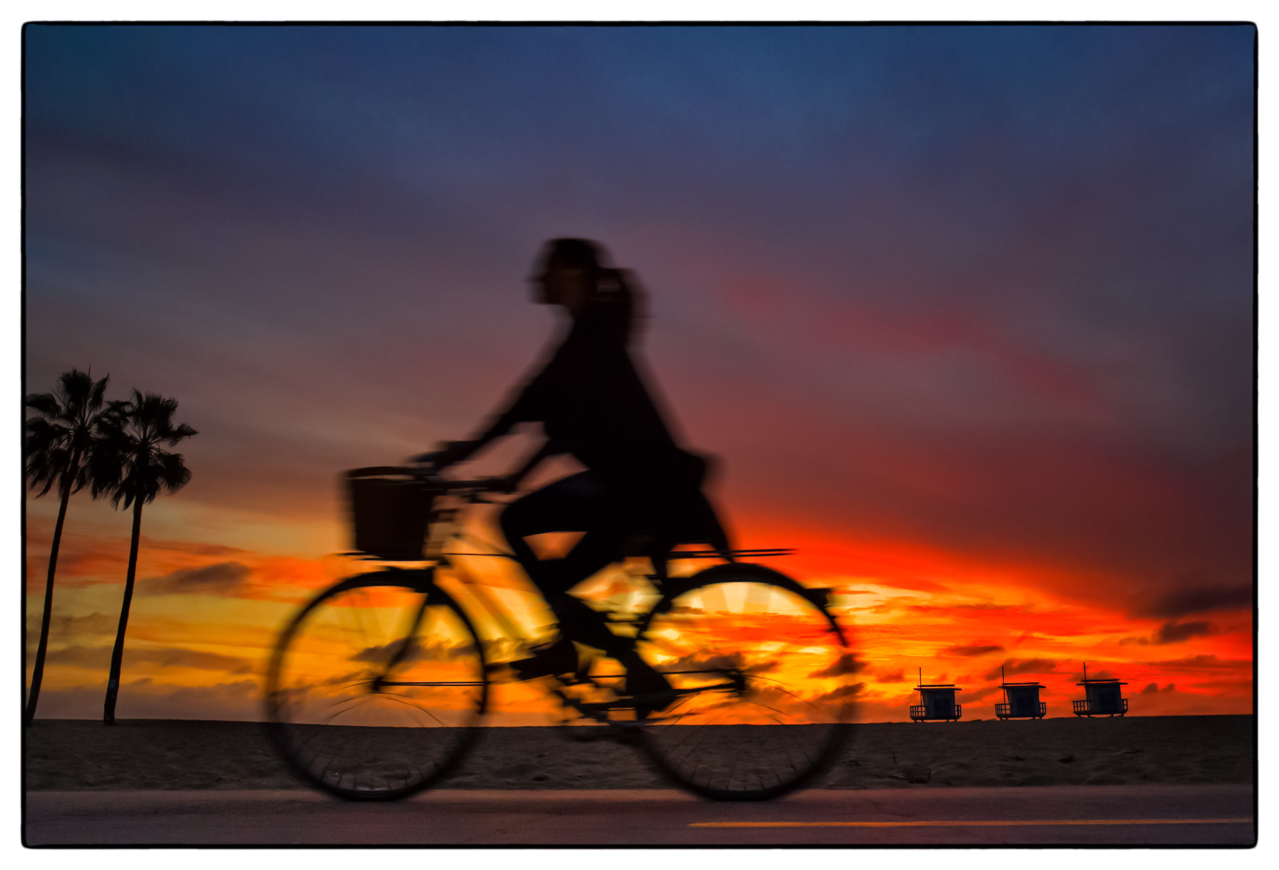 a-woman-on-her-bicycle-at-sunset-on-a-pathway-in-santa-monica-california