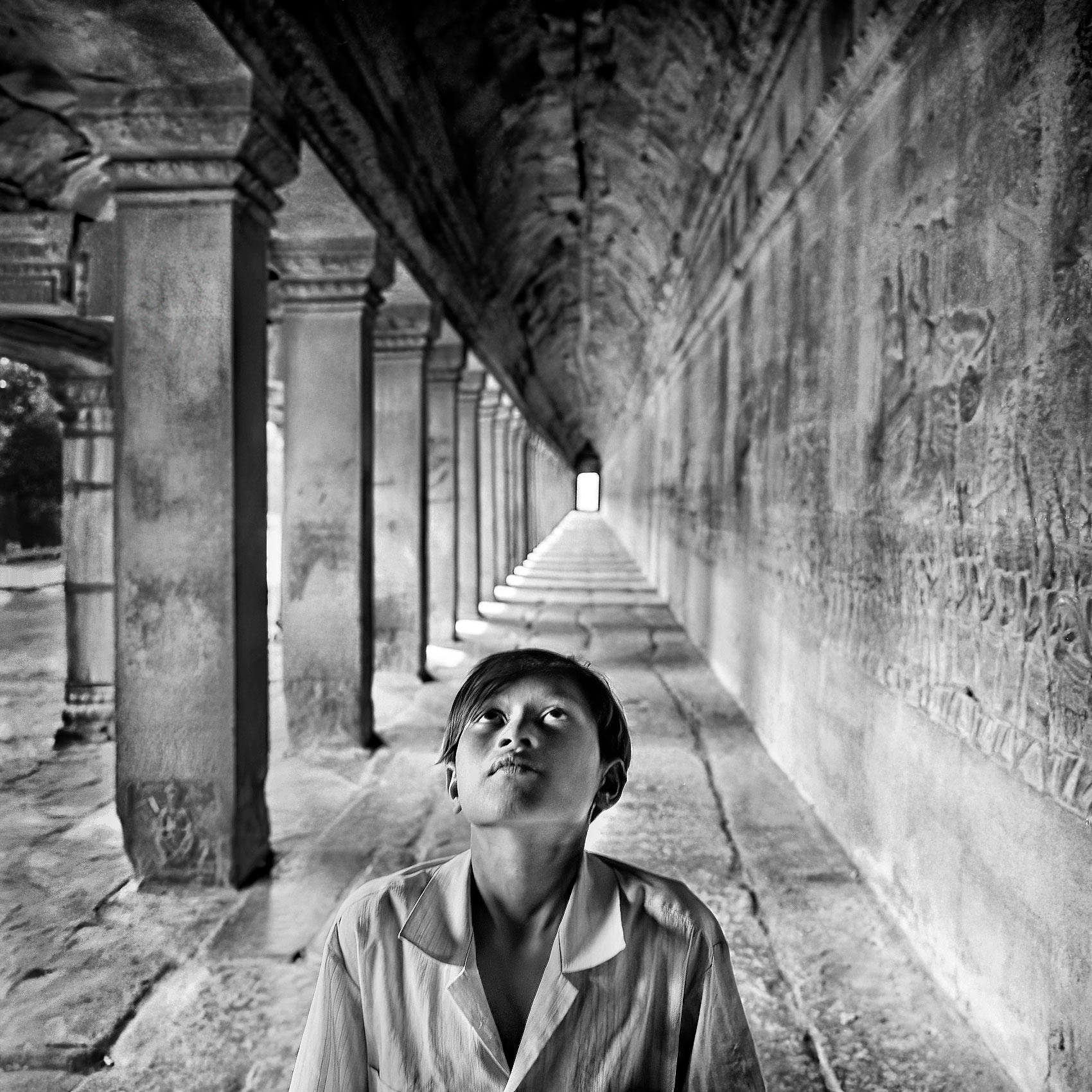 a-young-boy-gazes-up-at-the-ceiling-of-the-grand-palace-in-angkor-wat-cambodia