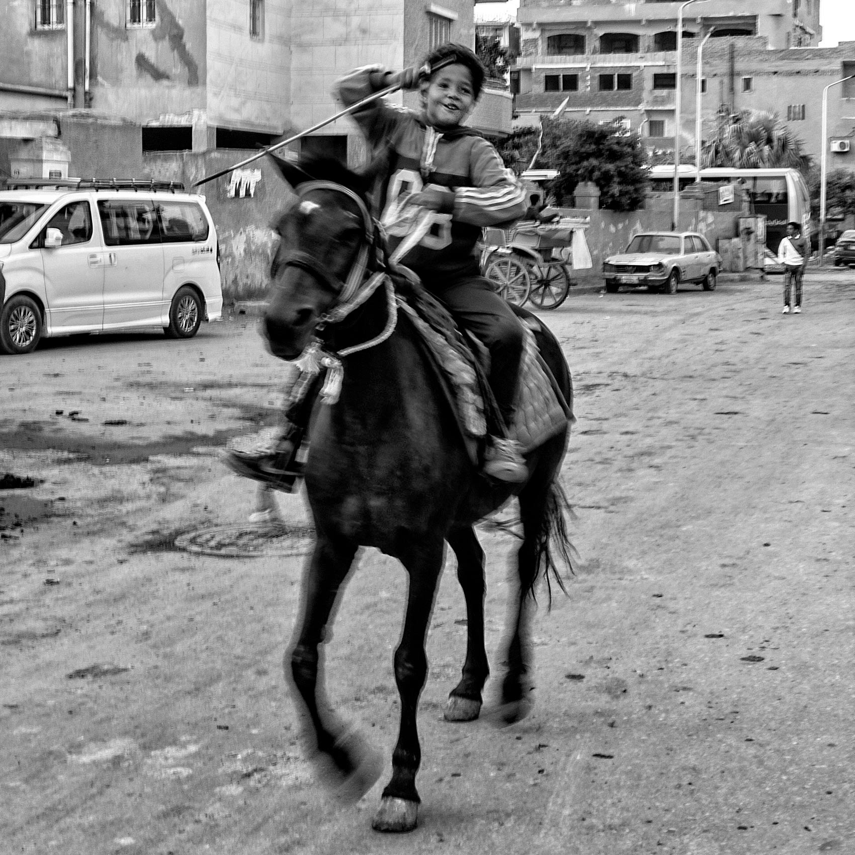 a young boy laughs while riding a horse on the streets of giza egypt