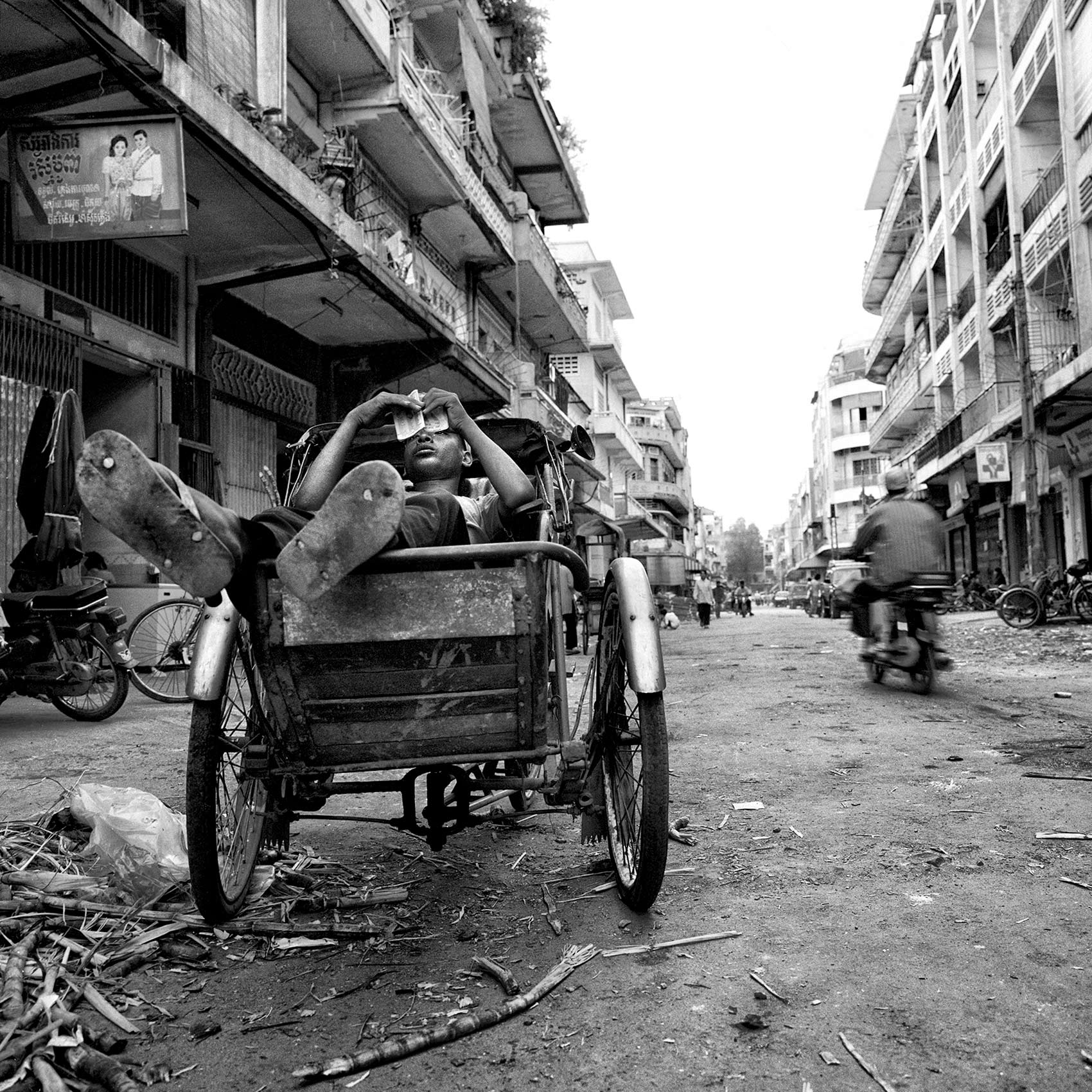 a-young-boy-takes-a-break-as-he-rests-inside-his-bicycle-taxi-in-phnom-penh-cambodia