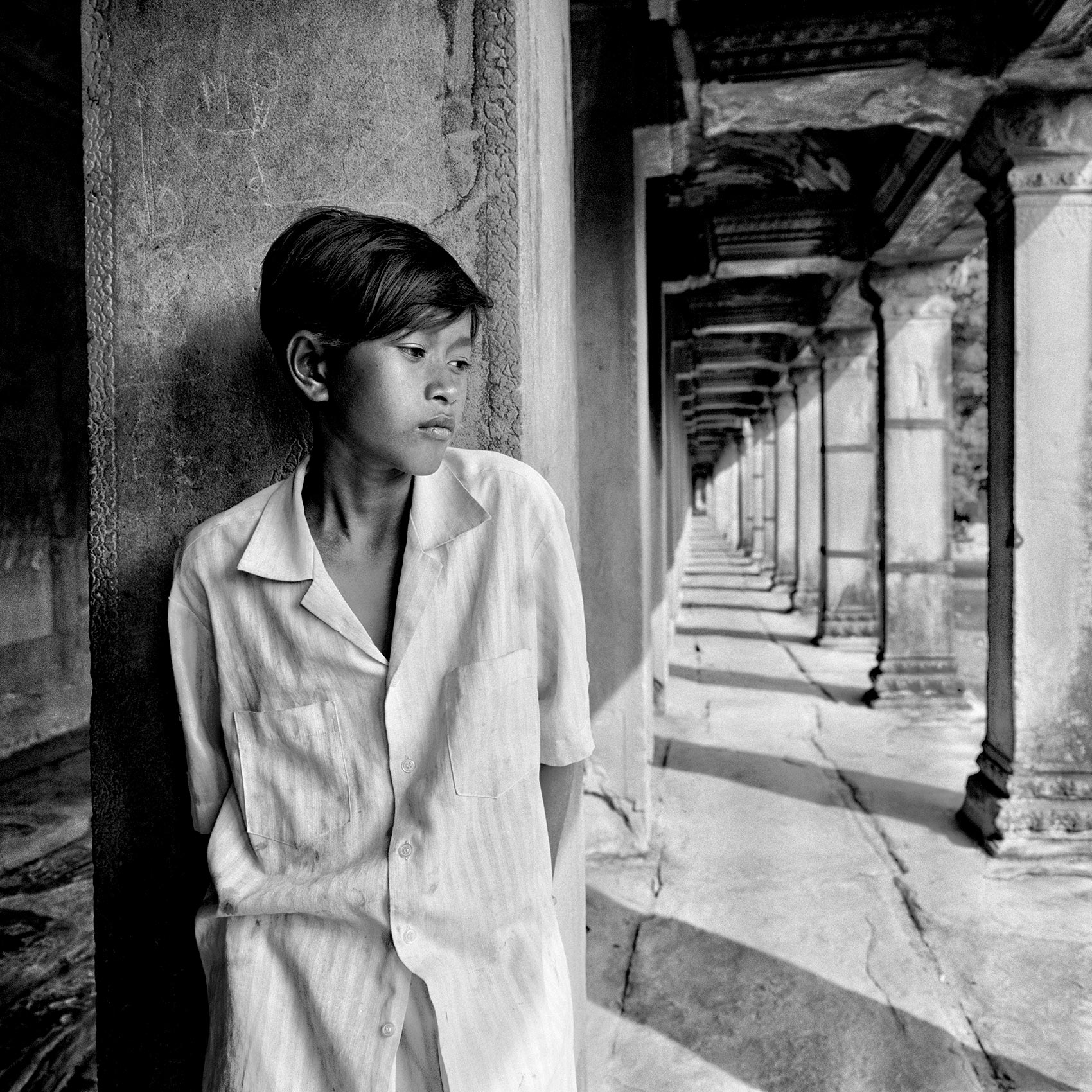 a-young-boy-who-begs-for-money-waits-in-the-early-morning-for-tourists-to-arrive-in-angkor-wat-cambodia