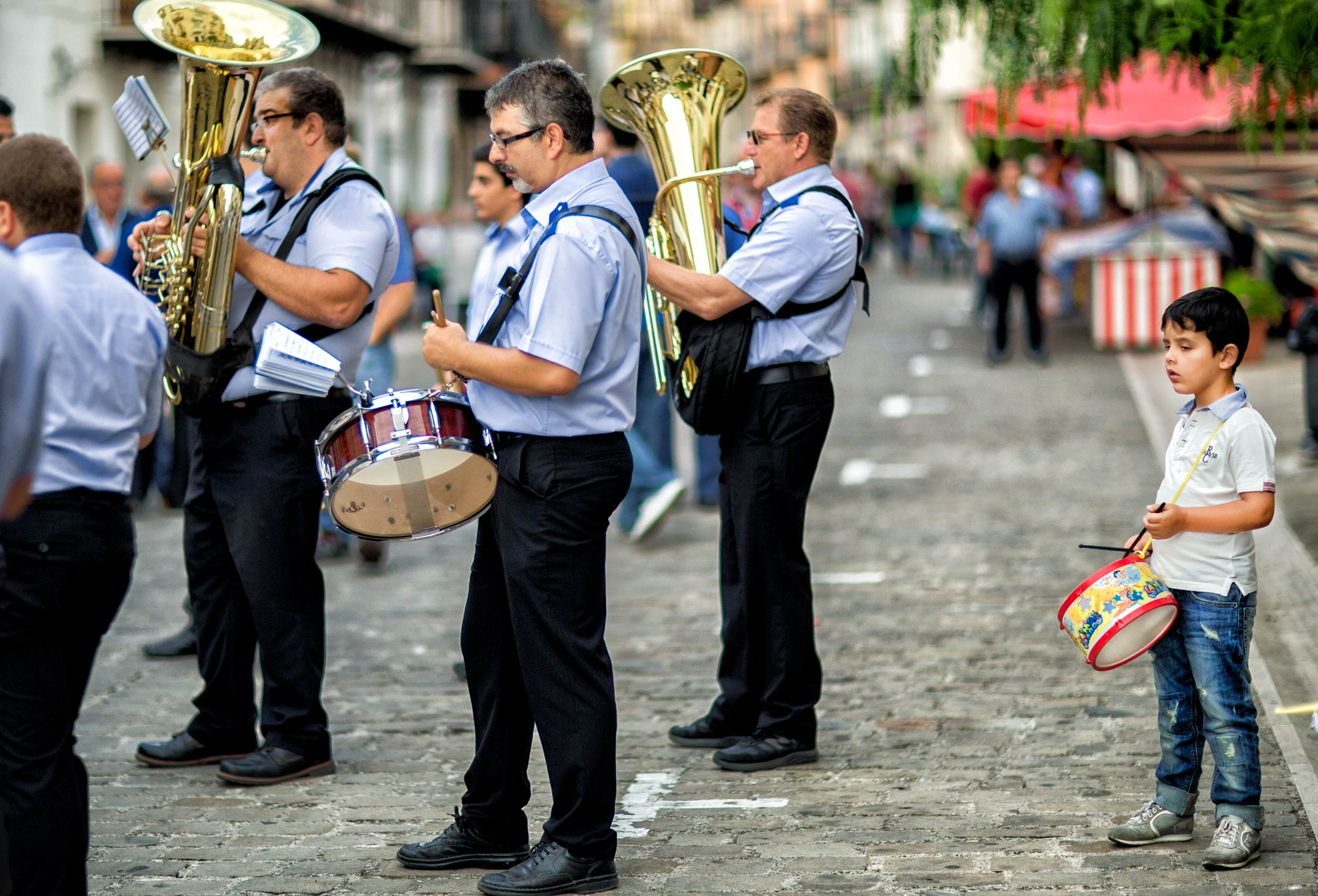 a-young-boy-with-his-toy-drum-joins-a-professional-band-on-the-streets-of-graterri-sicily