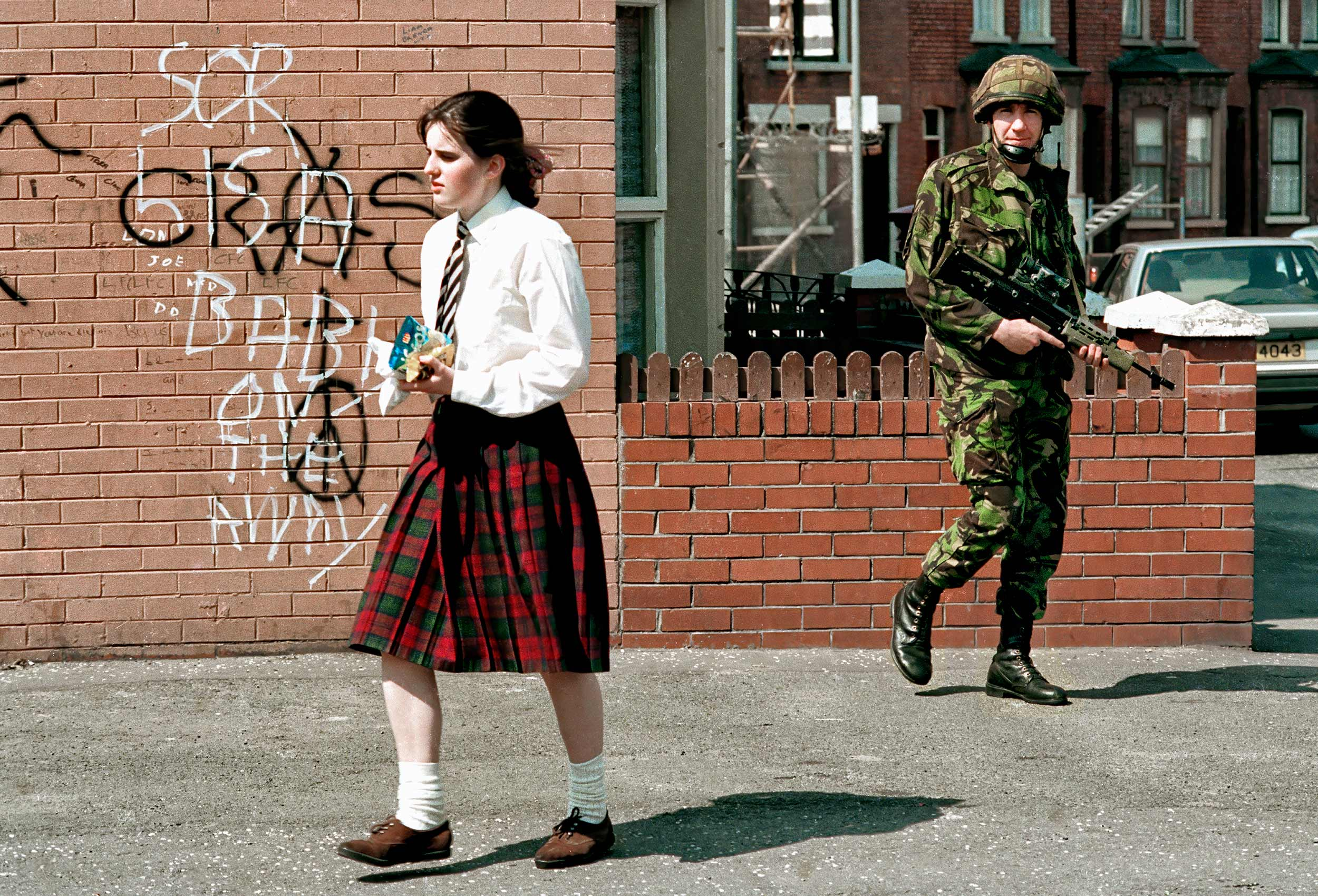 a-young-catholic-irish-school-girl-walks-past-a-british-soldier-on-falls-road-in-catholic-west-belfast