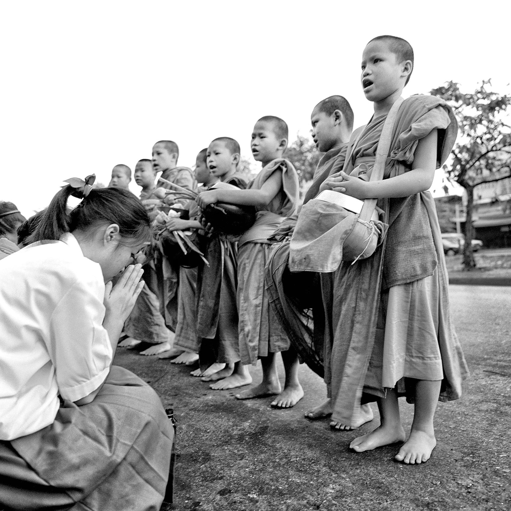 a-young-girl-bows-before-a-group-of-very-young-monks-on-a-street-in-northern-thailand
