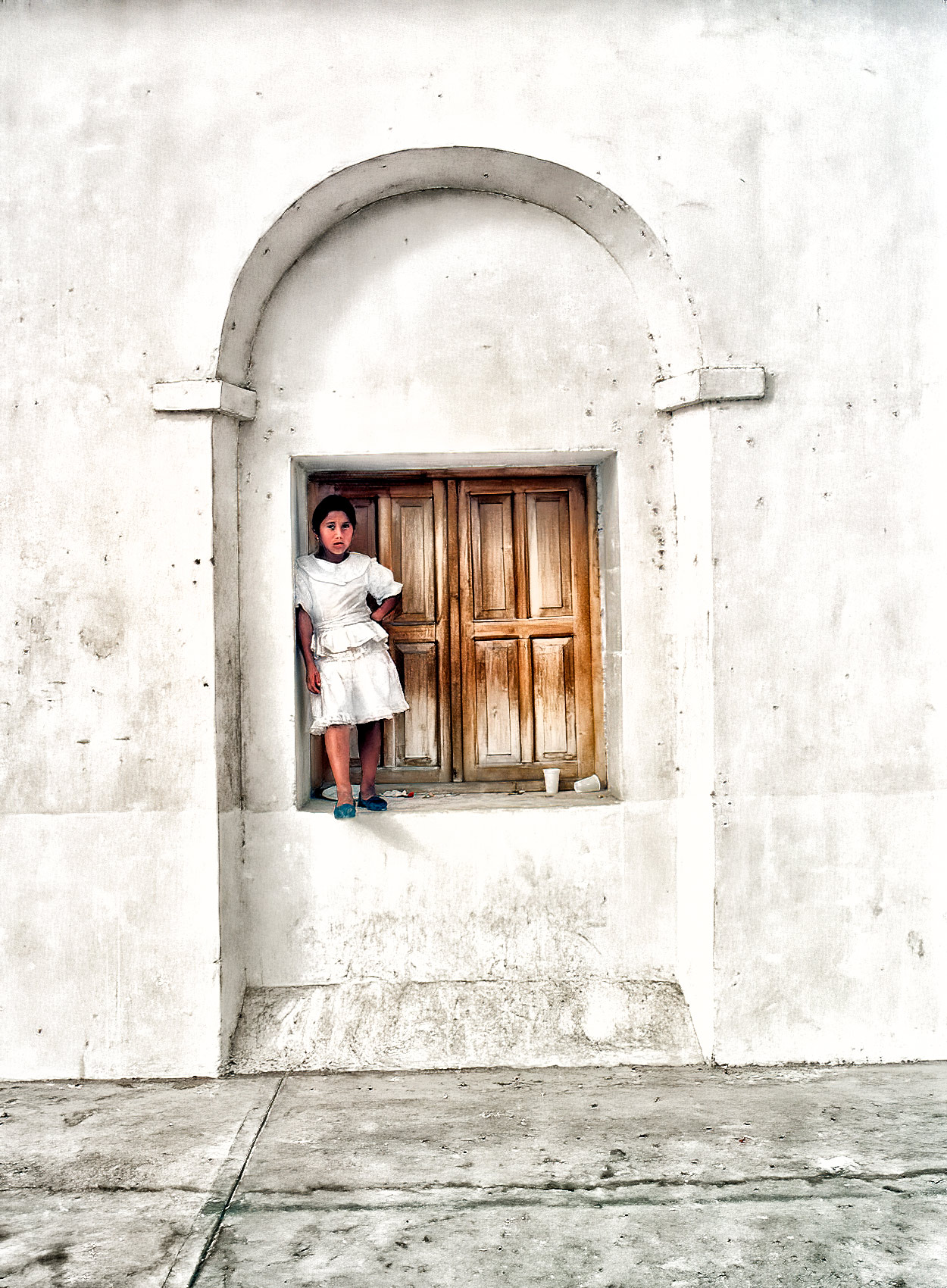 a-young-guatemalan-girl-stands-in-a-windowsill-to-watch-a-festival-in-flores