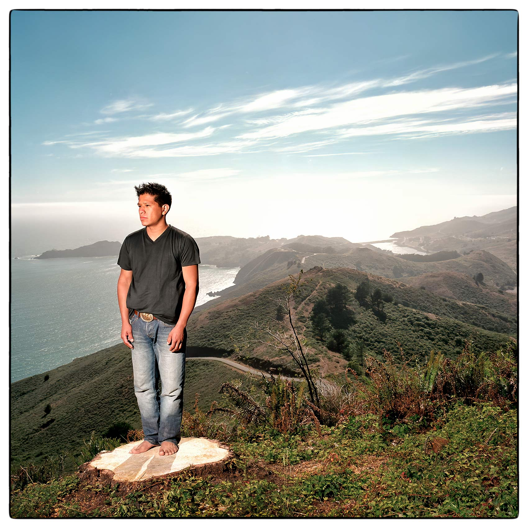 a-young-man-stands-on-a-wood-stump-as-he-looks-out-over-san-francisco-bay