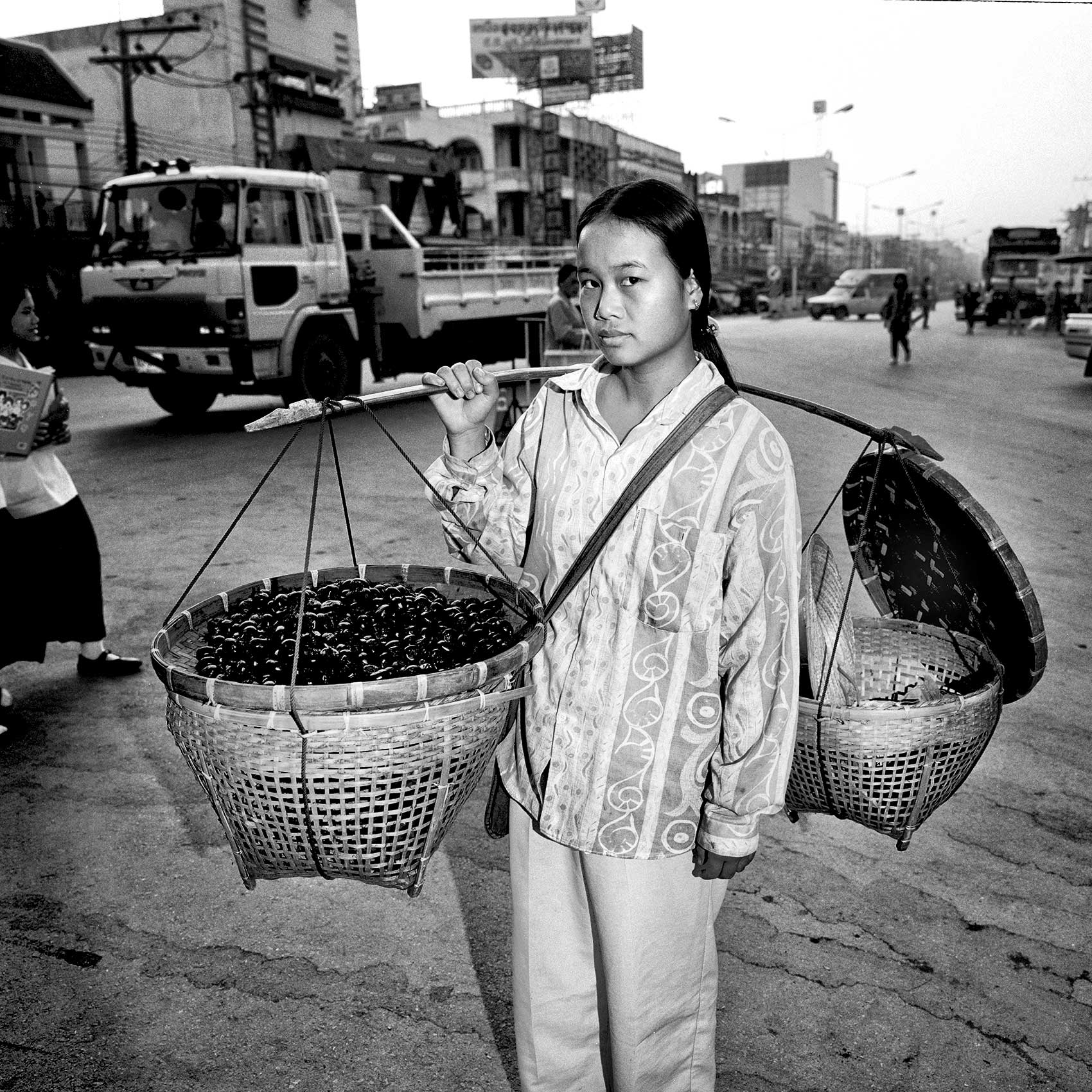 a-young-woman-carries-her-food-to-the-market-to-sell-in-phnom-pehn-cambodia
