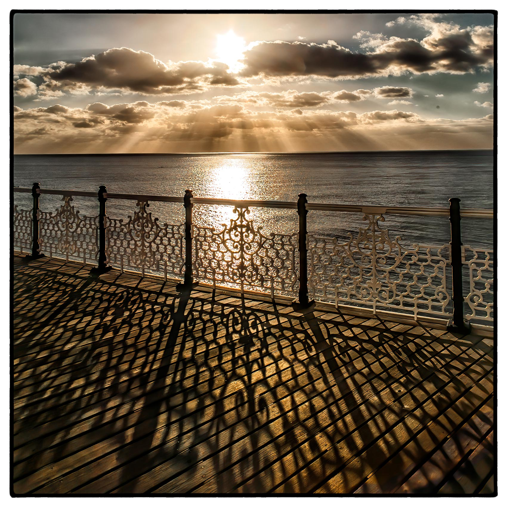 a brilliant sun breaks through the clouds  as it sets over brighton pier in southern england