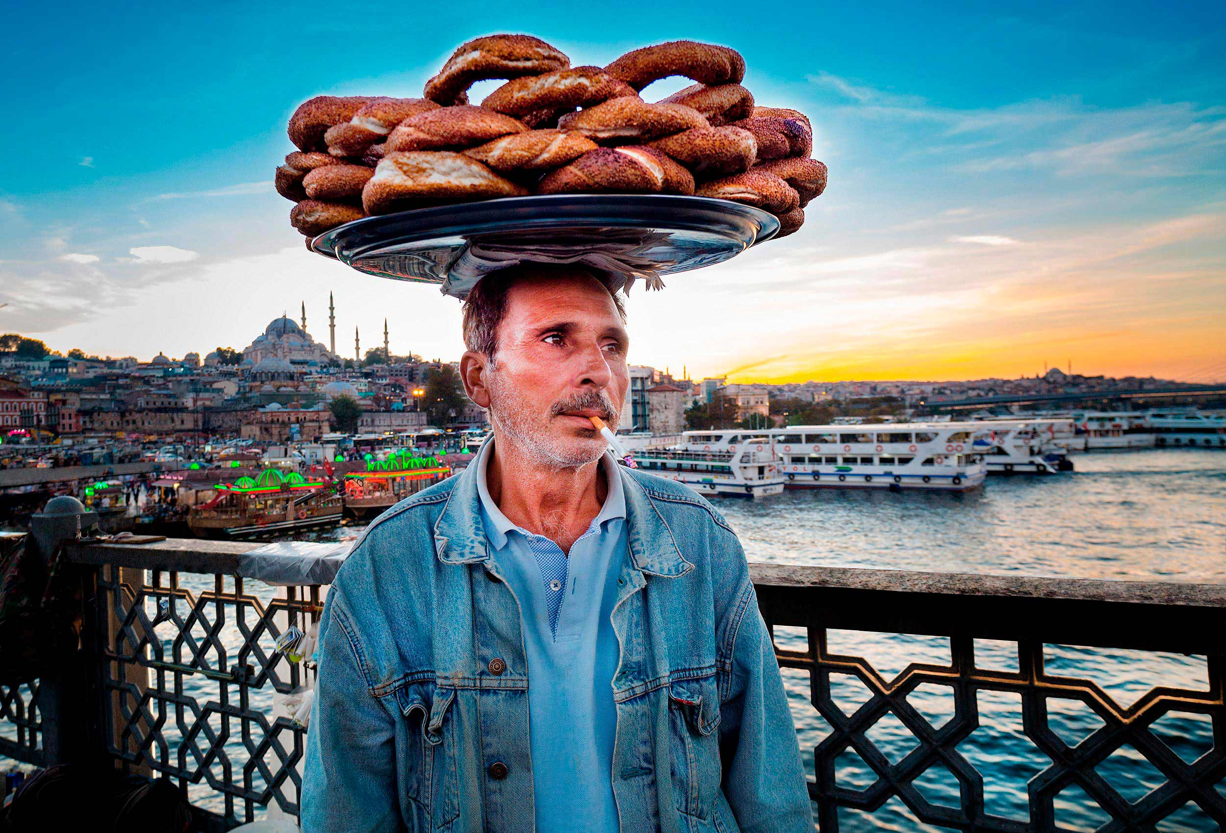 an amazing turkish travel photo of a simit street vendor balancing a tray on his head