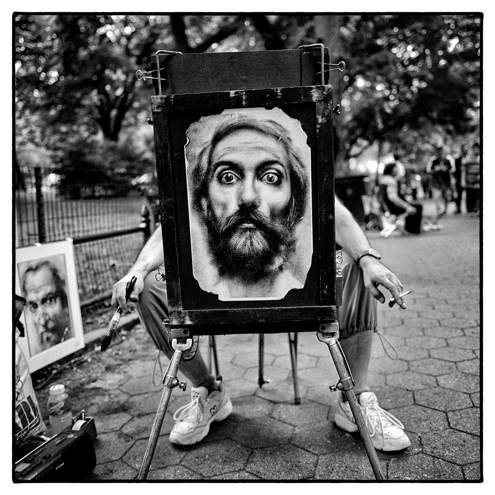 an-artist-in-central-park-in-new-york-sits-behind-a-painting-of-a-face