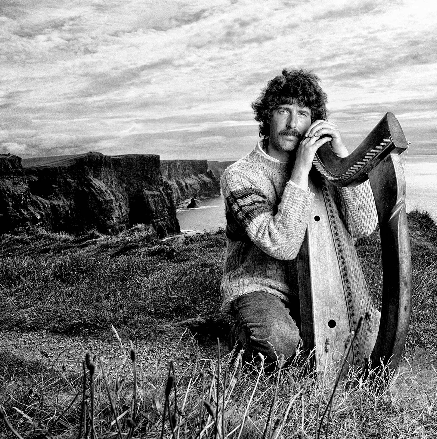 an-irish-man-poses-with-his-harp-high-up-on-the-scenic-cliffs-of-moher