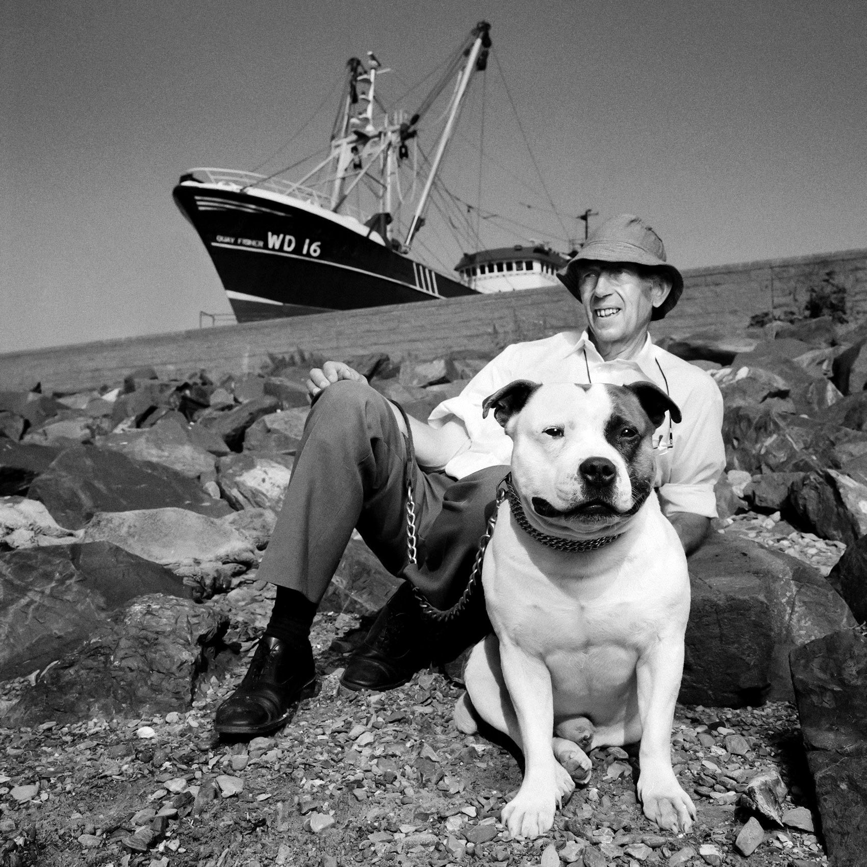 an-irishman-and-his-large-dog-sit-on-the-rocky-shoreline-in-howth-ireland