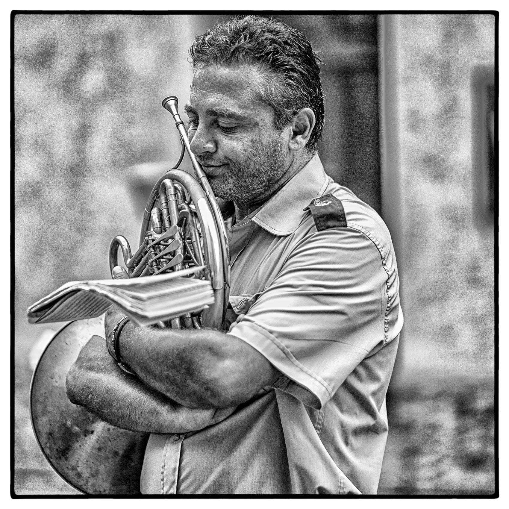 an-italian-man-holds-his-french-horn-tightly-as-he-appears-deep-in-thought-while-reading-his-music