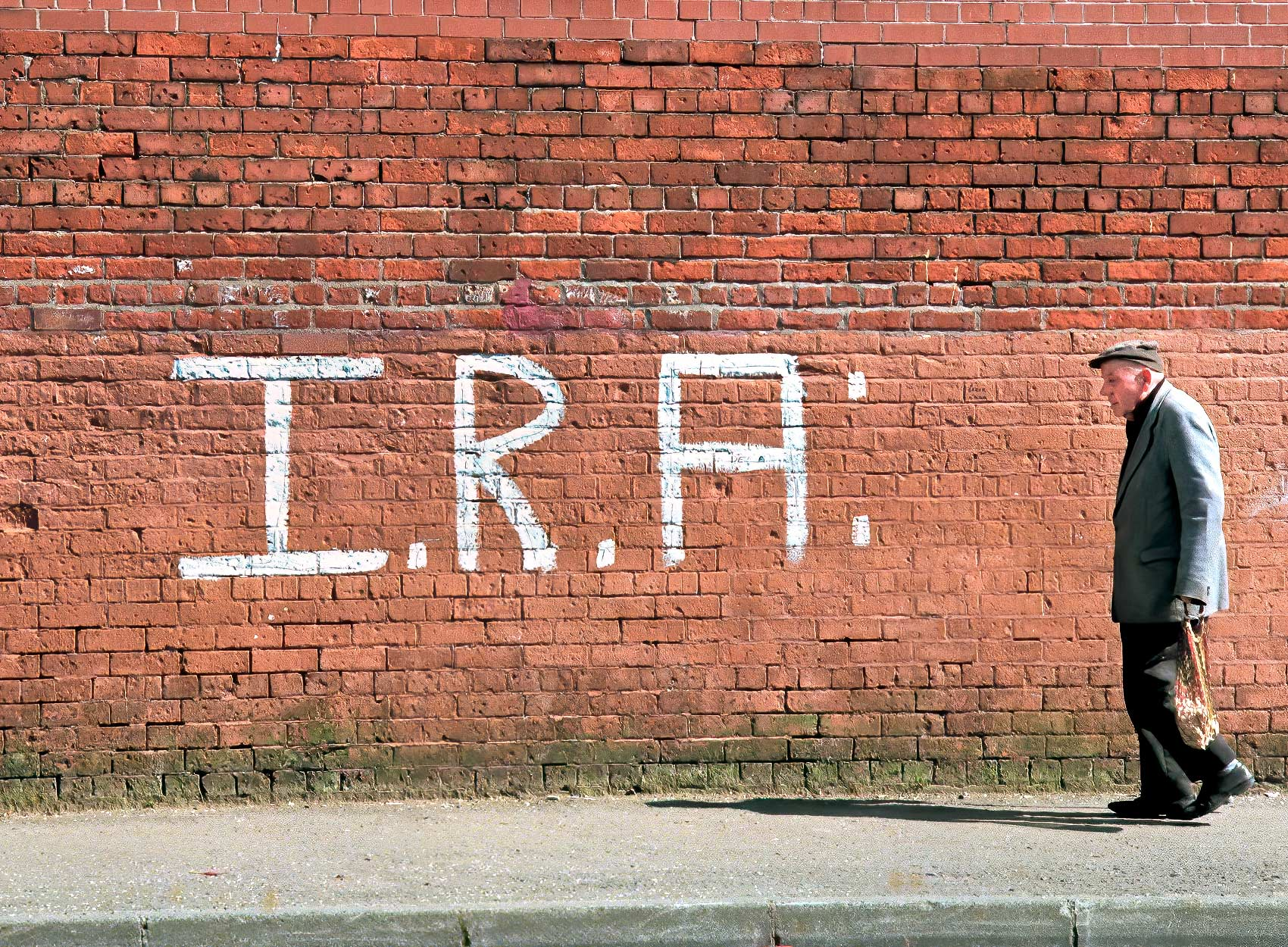 an-old-man-walks-past-irish-republican-army-graffitti-on-a-wall-in-catholic-west-belfast