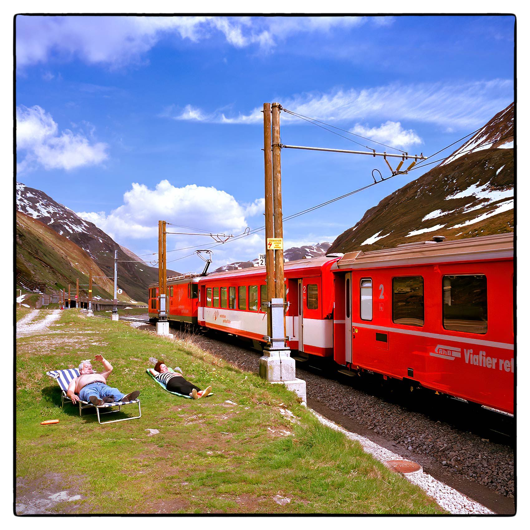 an-older-couple-suntan-next-to-the-train-tracks-high-in-the-swiss-alps
