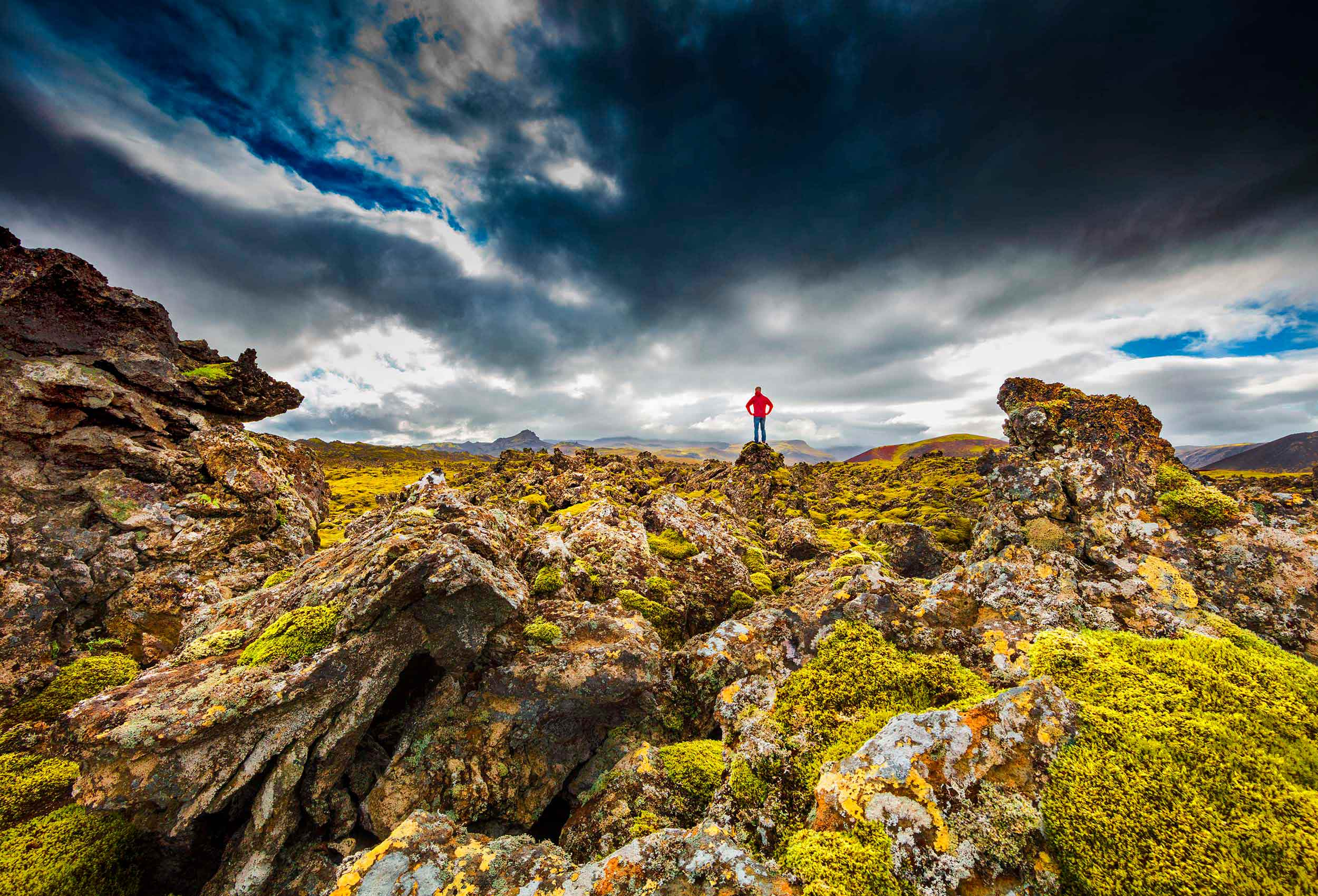 green moss covered lava fields with a man on top of them in Iceland by amazing travel photographer John Hryniuk