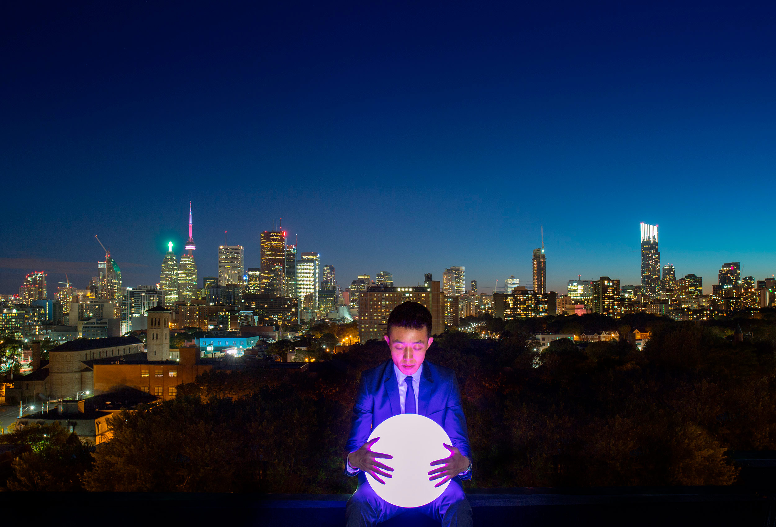 a man with a globe of light and the night skyline of toronto canada behind him