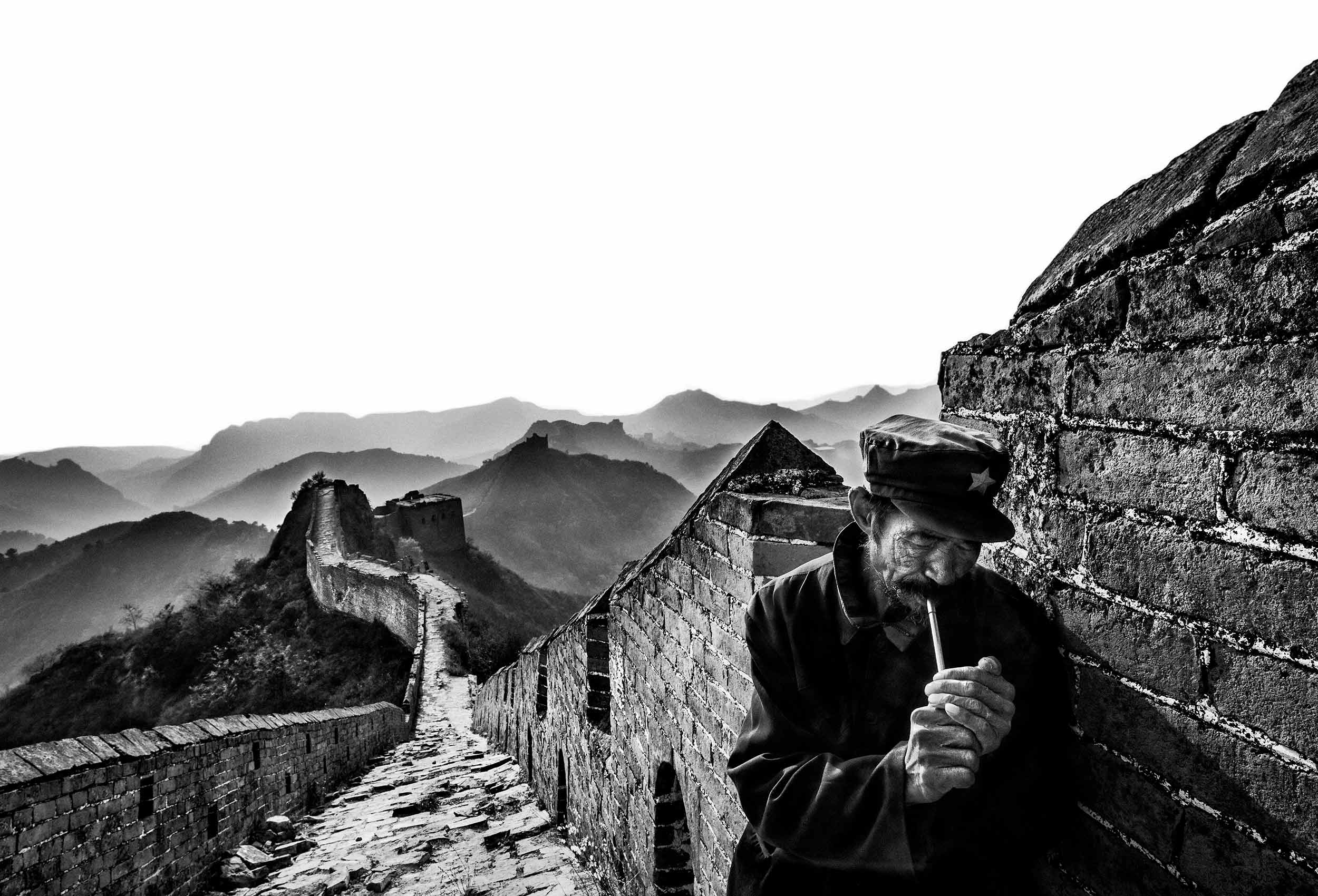 a guard smokes  his pipe on the great wall of china in simatai