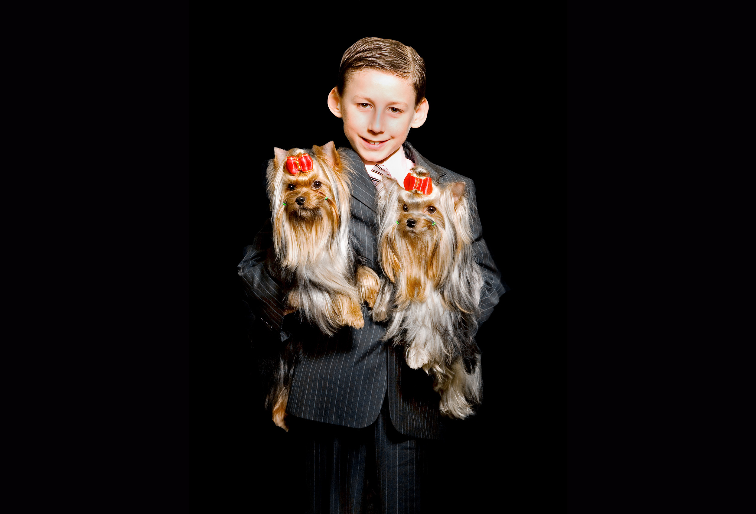 a boy poses with his winning dogs at the canadian national purina dog show in toronto
