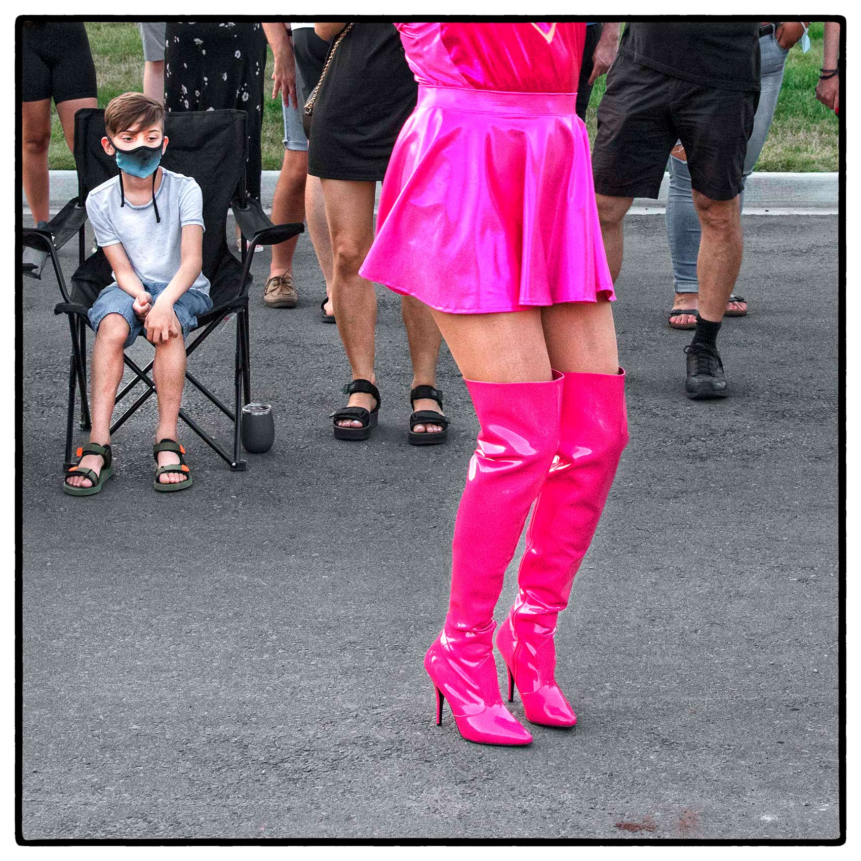 A young boy stares a drag queen by Toronto editorial photographer John Hryniuk