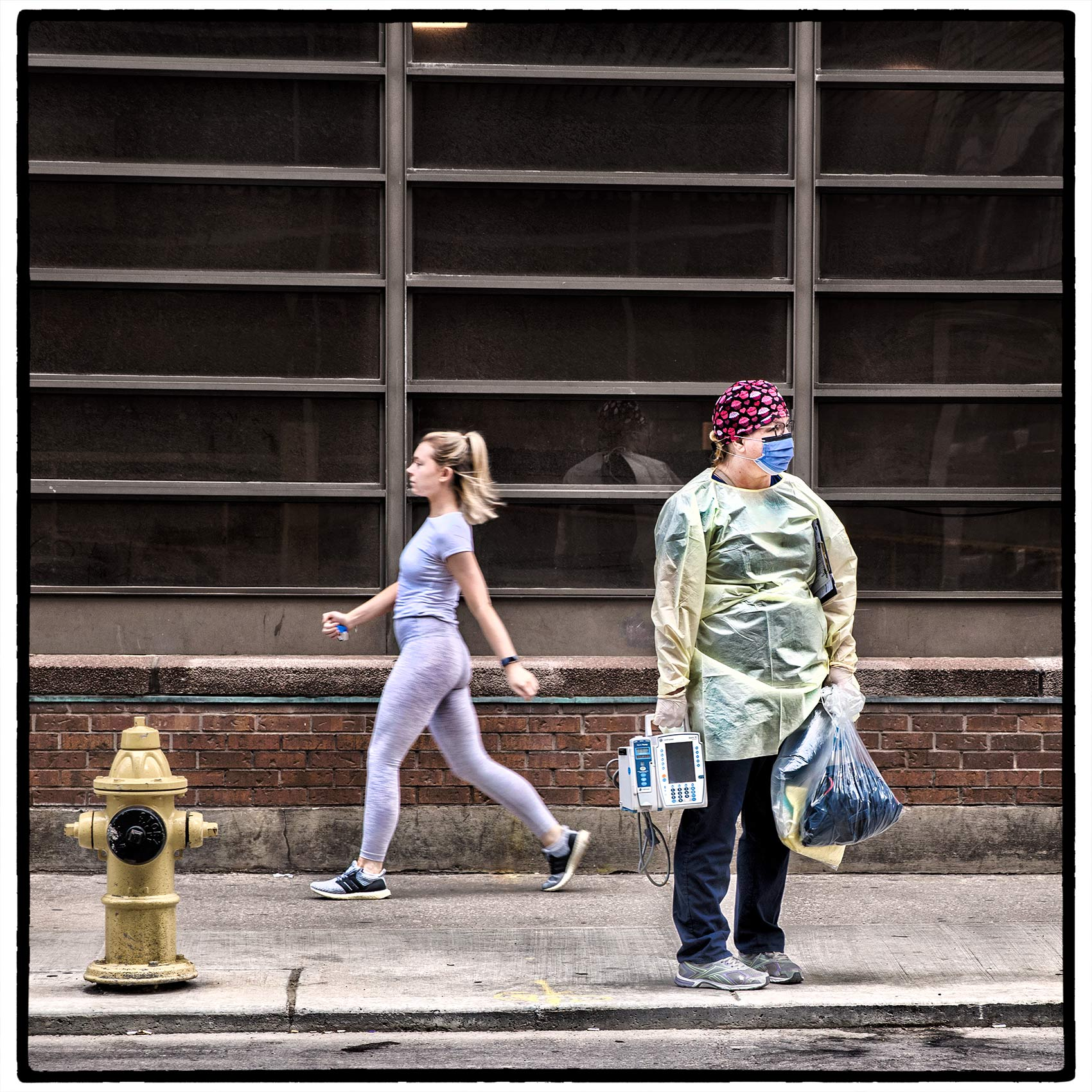 covid-nurse-wearing-personal-protective-equipment-with-young-woman-wearing-yoga-outfit-behind-her