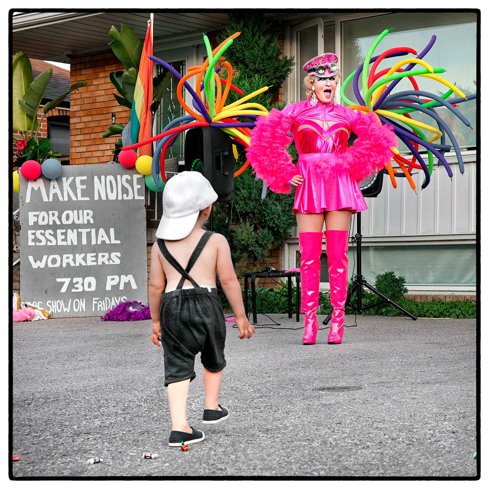 a young boy excitedly walks towards a drag queen in north york during the pandemic