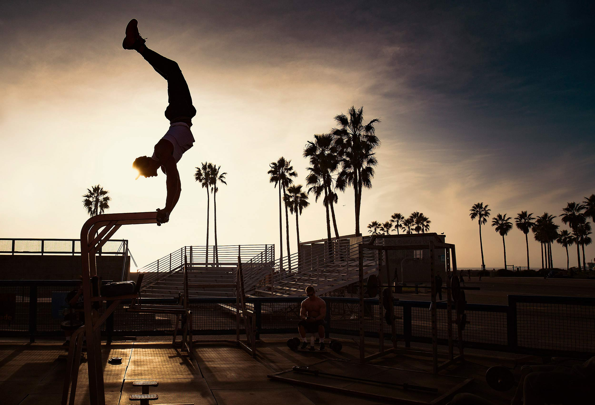A man at sunset working out at Muscle Beach by award winning travel photographer