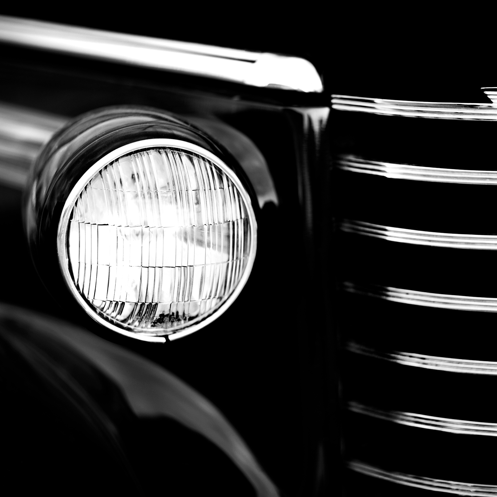 a black and white photo of a head light on a 1946 oldsmobile automobile