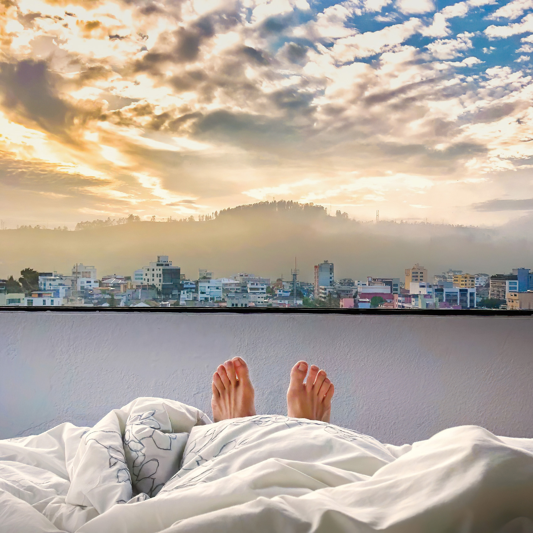 feet-stick-out-from-the-end-of-a-bed-as-the-sun-rising-over-the-city-of-quito-ecuador-appear-behind-them