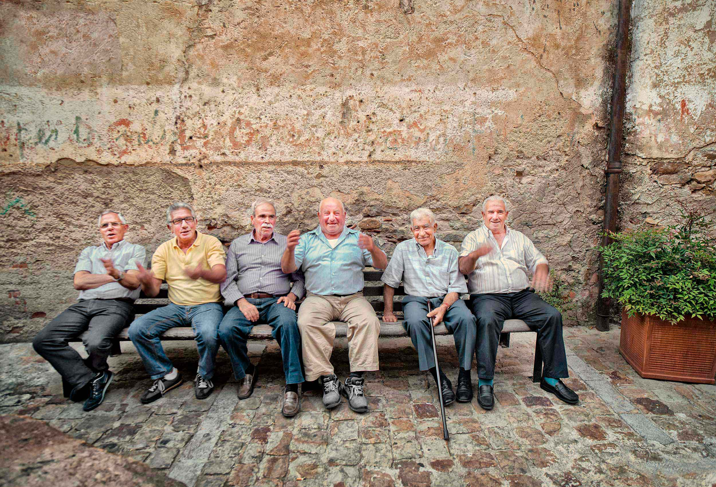 a photo of old men laughing while gossiping in sicilian town square in italy