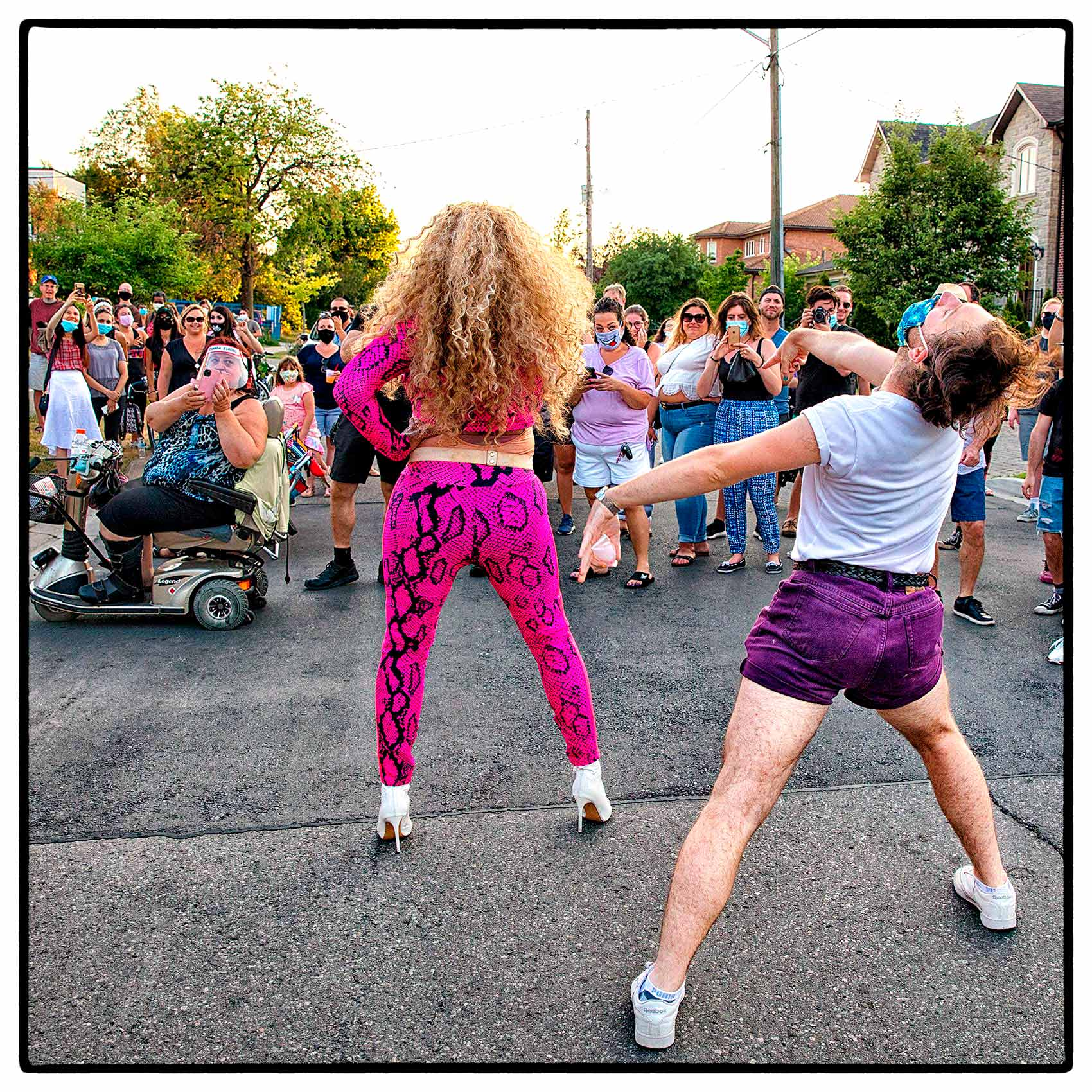 a man dancing behind a drag queen during a street show in north york in toronto