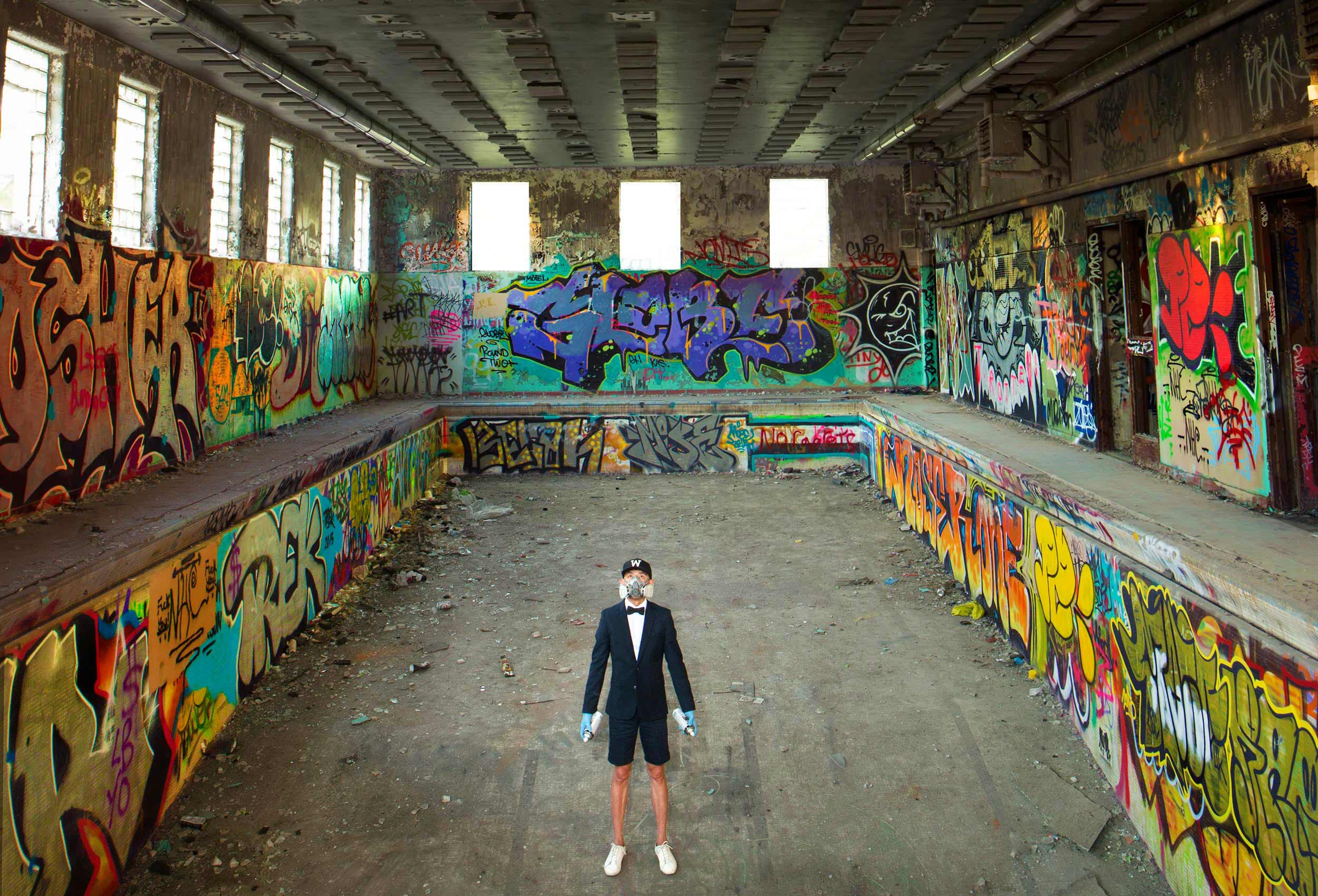 a graffitti artist poses in an empty swimming pool in toronto