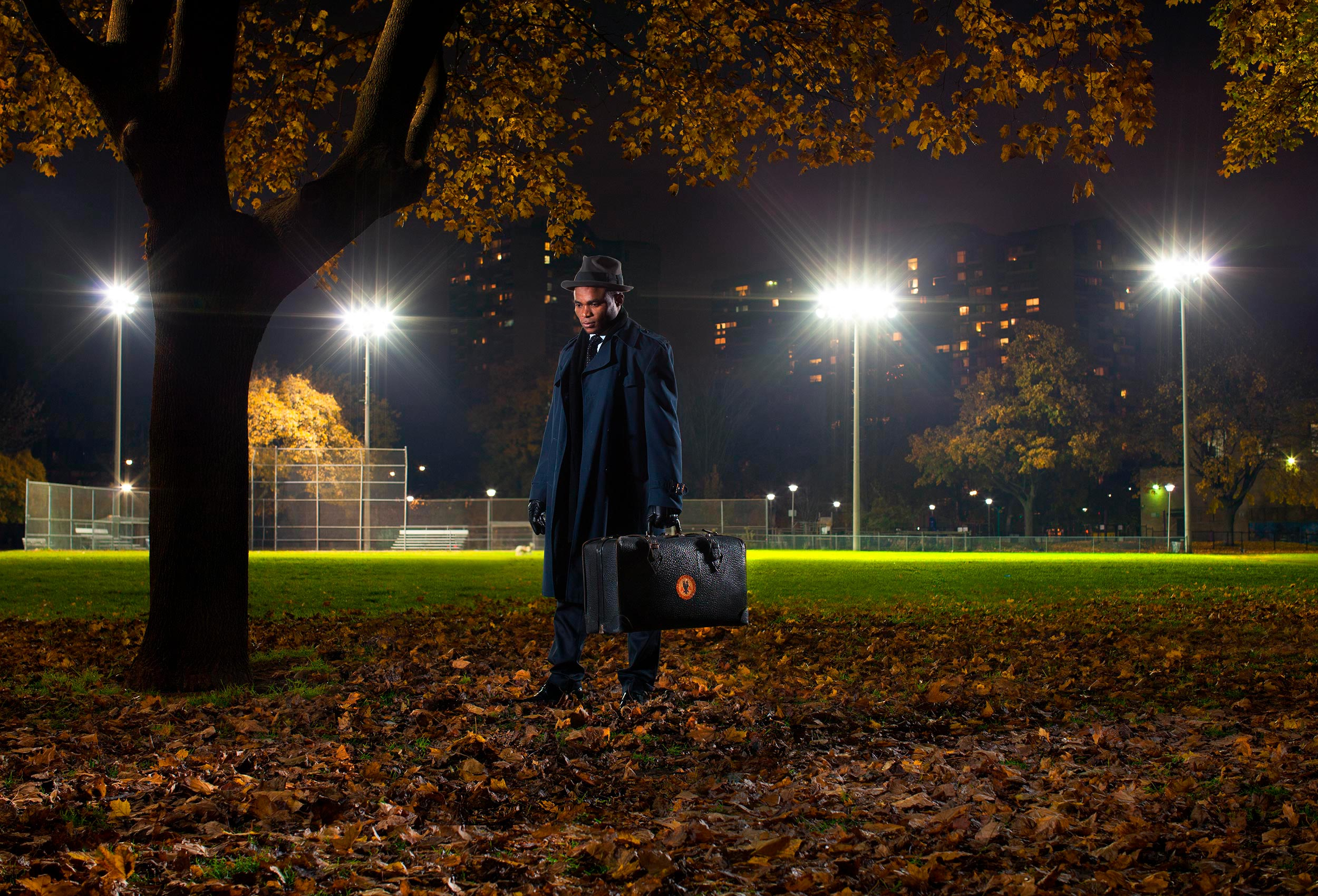 a man in a suit poses for a photo at night in a downtown toronto park