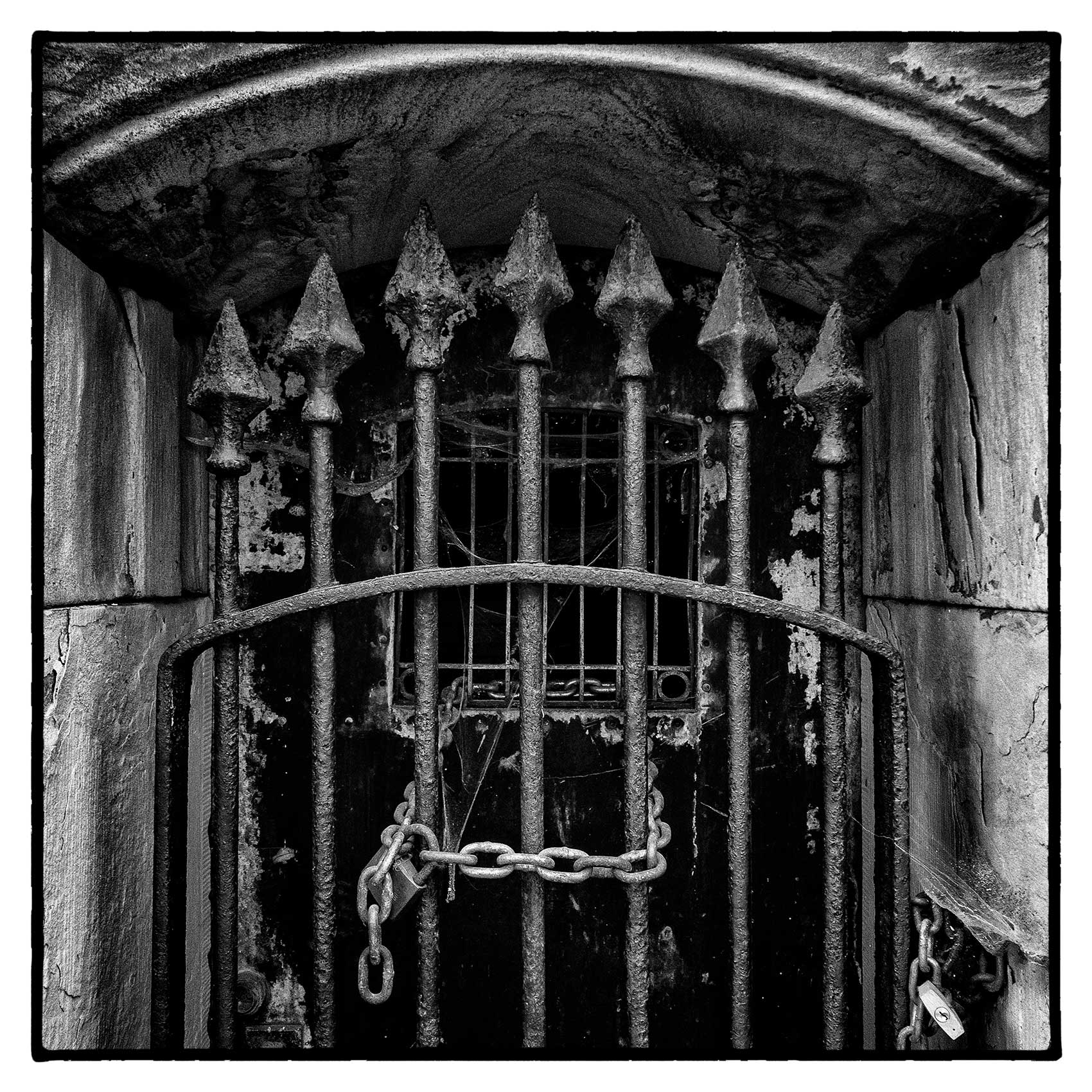 a locked up old iron gate to a crypt at Torontos St. James Cemetery