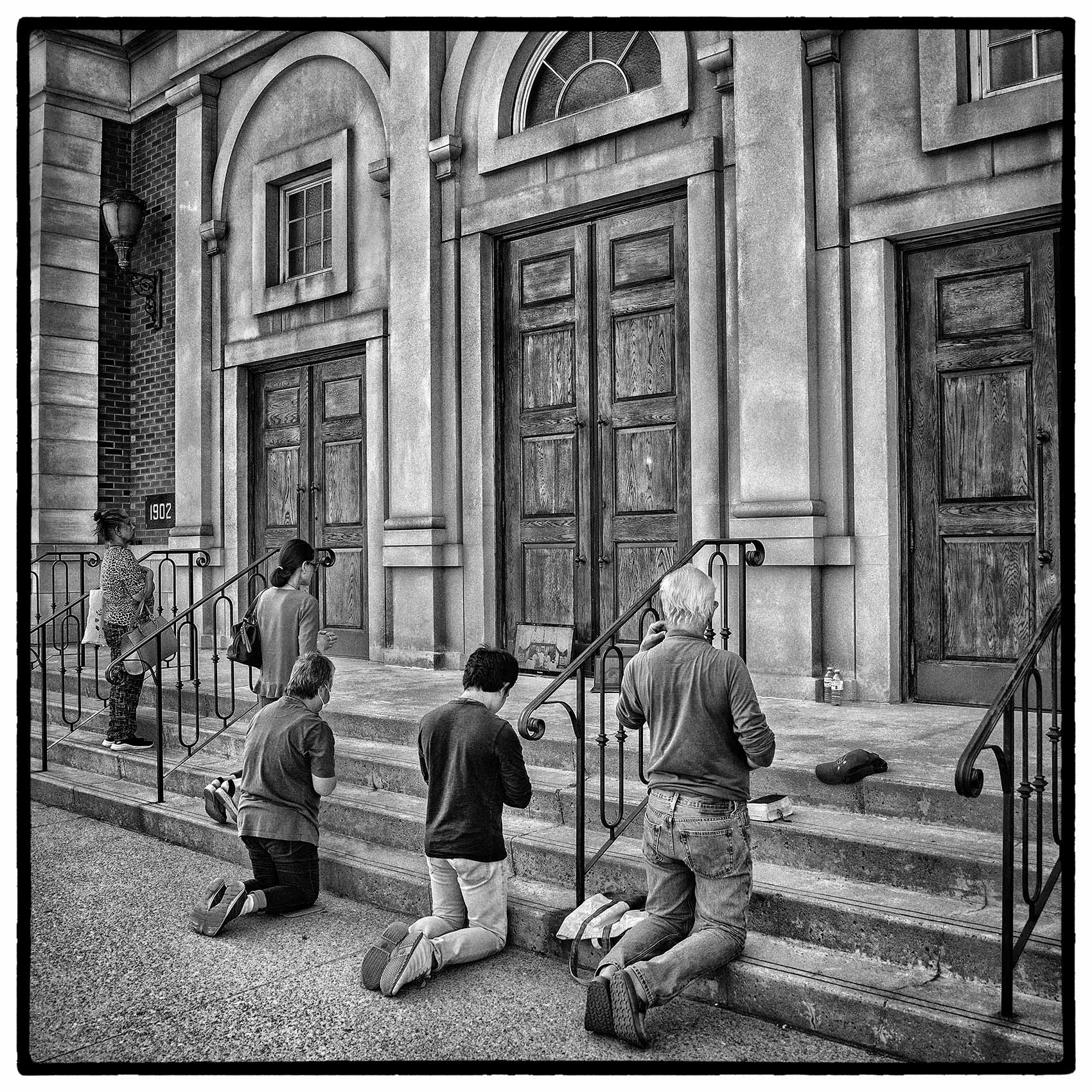 Parishioners pray on the stairs of a Toronto church during the Covid-19 Pandemic