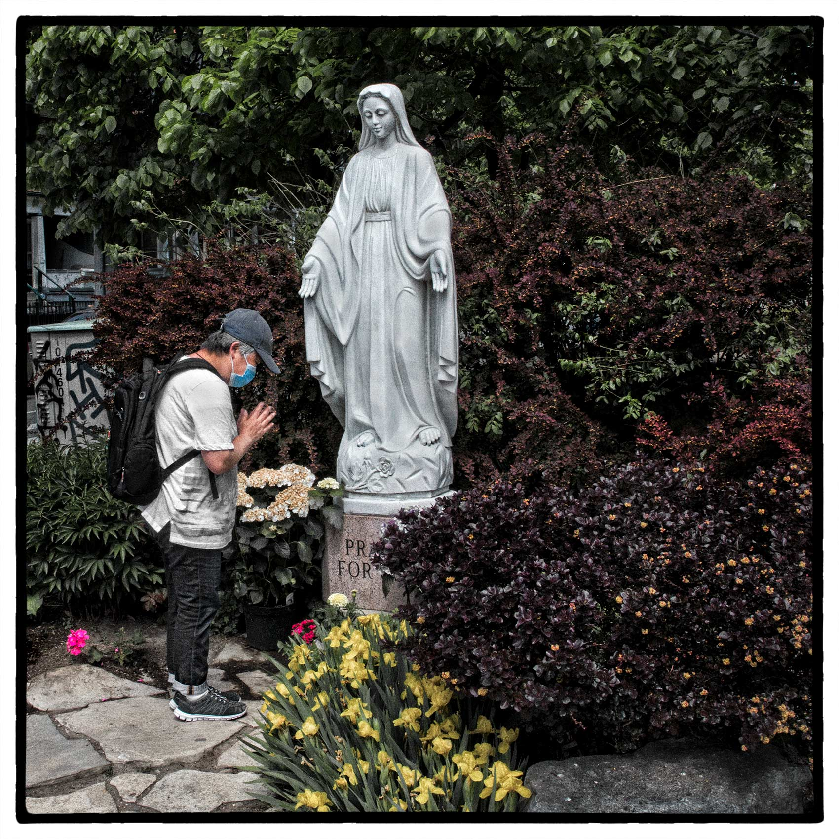 a woman prays to a statue of the Virgin Mary outside holy family church during the pandemic