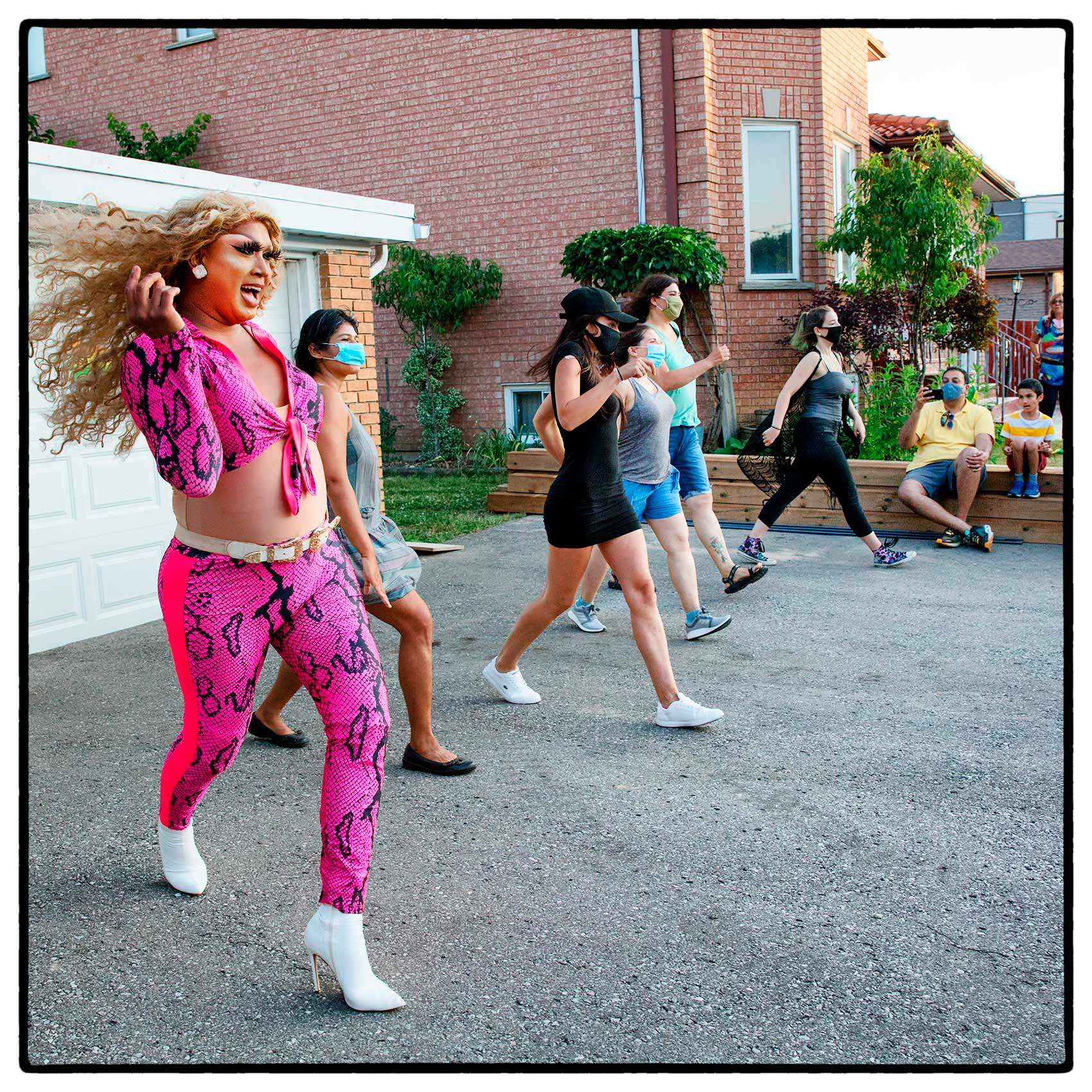 a drag queen dancing with woman on street during a suburban show in toronto
