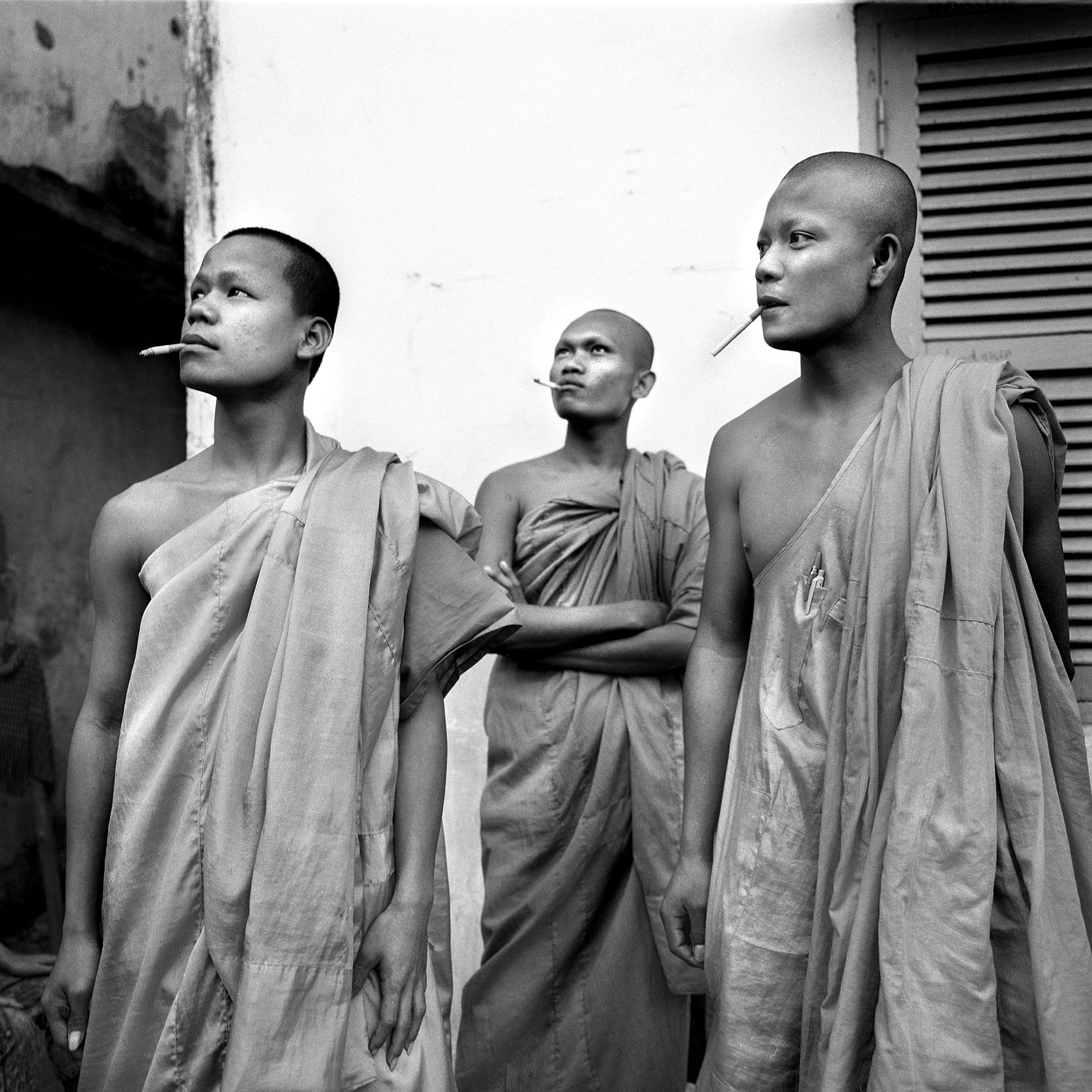 three monks pose for a photo as they smoke cigarettes in phnom penh cambodia