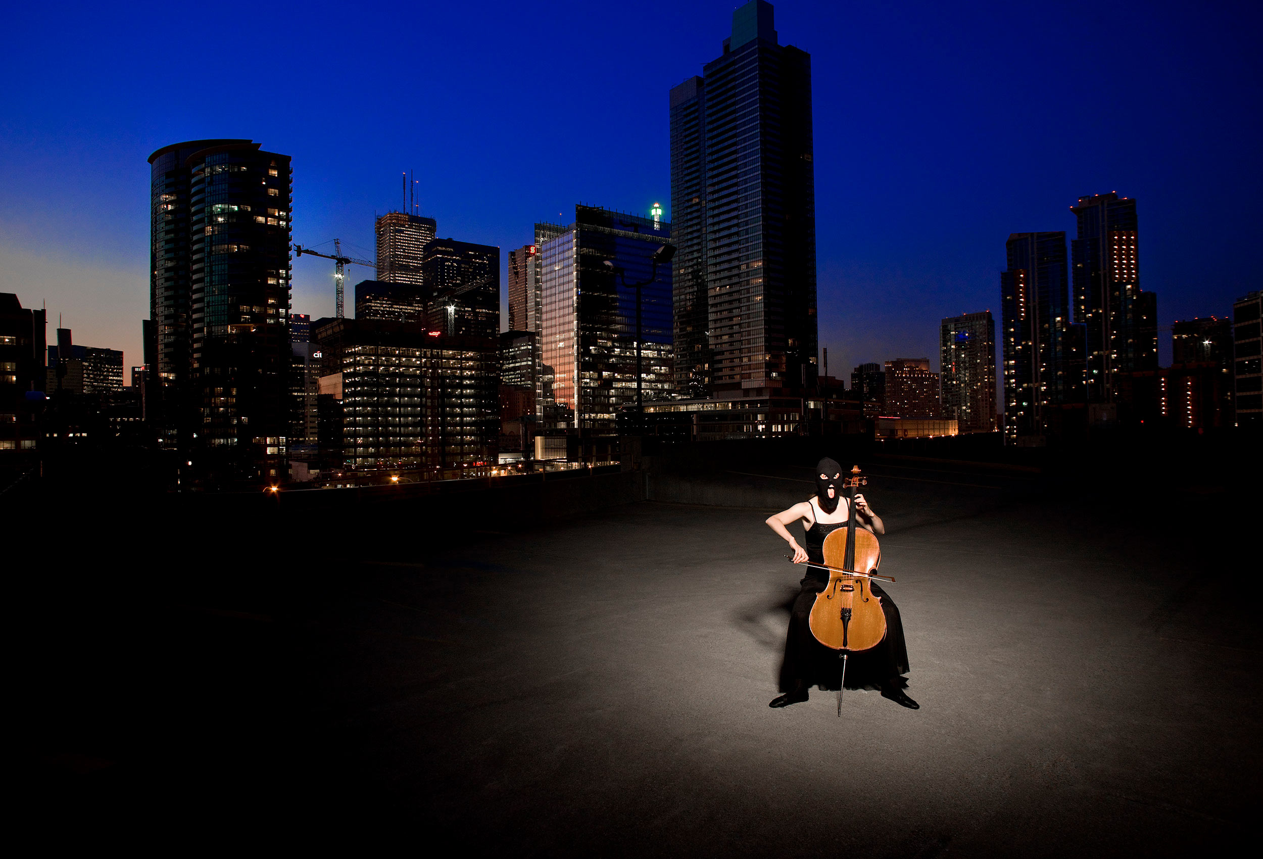 a women wearing a ski mask plays the cello in front of the toronto city skyline
