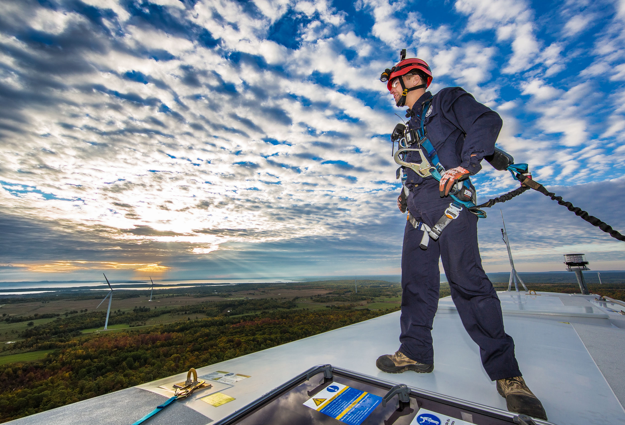 a northland power employee standing atop a ge windmill on manitoulin island