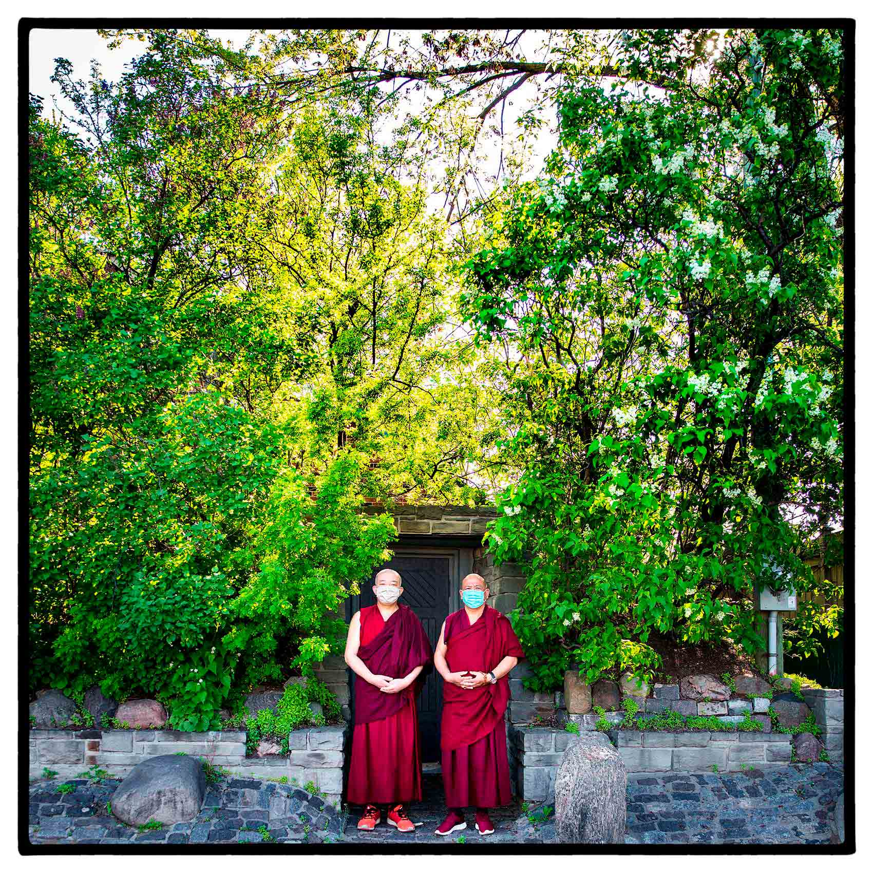 two-tibetan-monks-pose-for-a-photo-in-their-robes-and-face-masks-in-Toronto