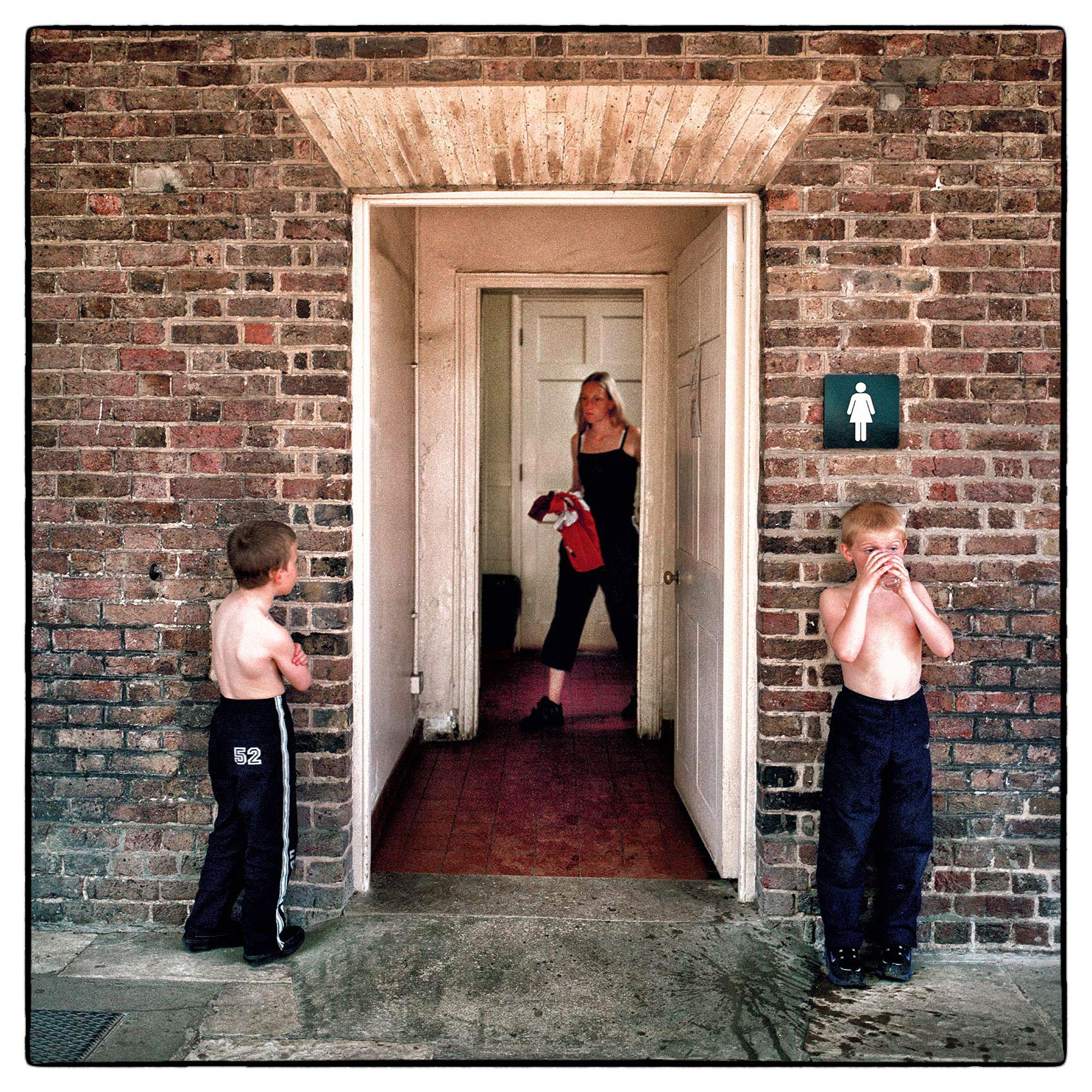 two-boys-wait-for-their-mother-outside-a-bathroom-in-londons-hampstead-heath