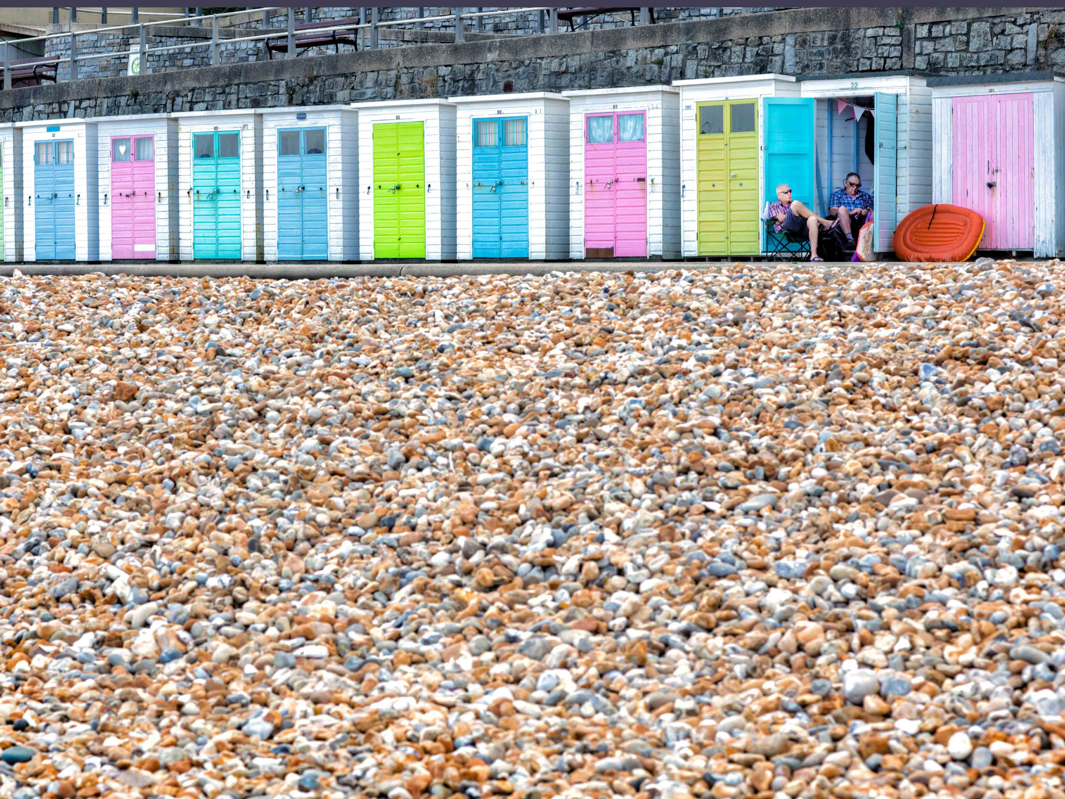 two-men-sit-outside-their-beach-hut-in-the-british-sea-side-town-of-lyme-regis-in-england