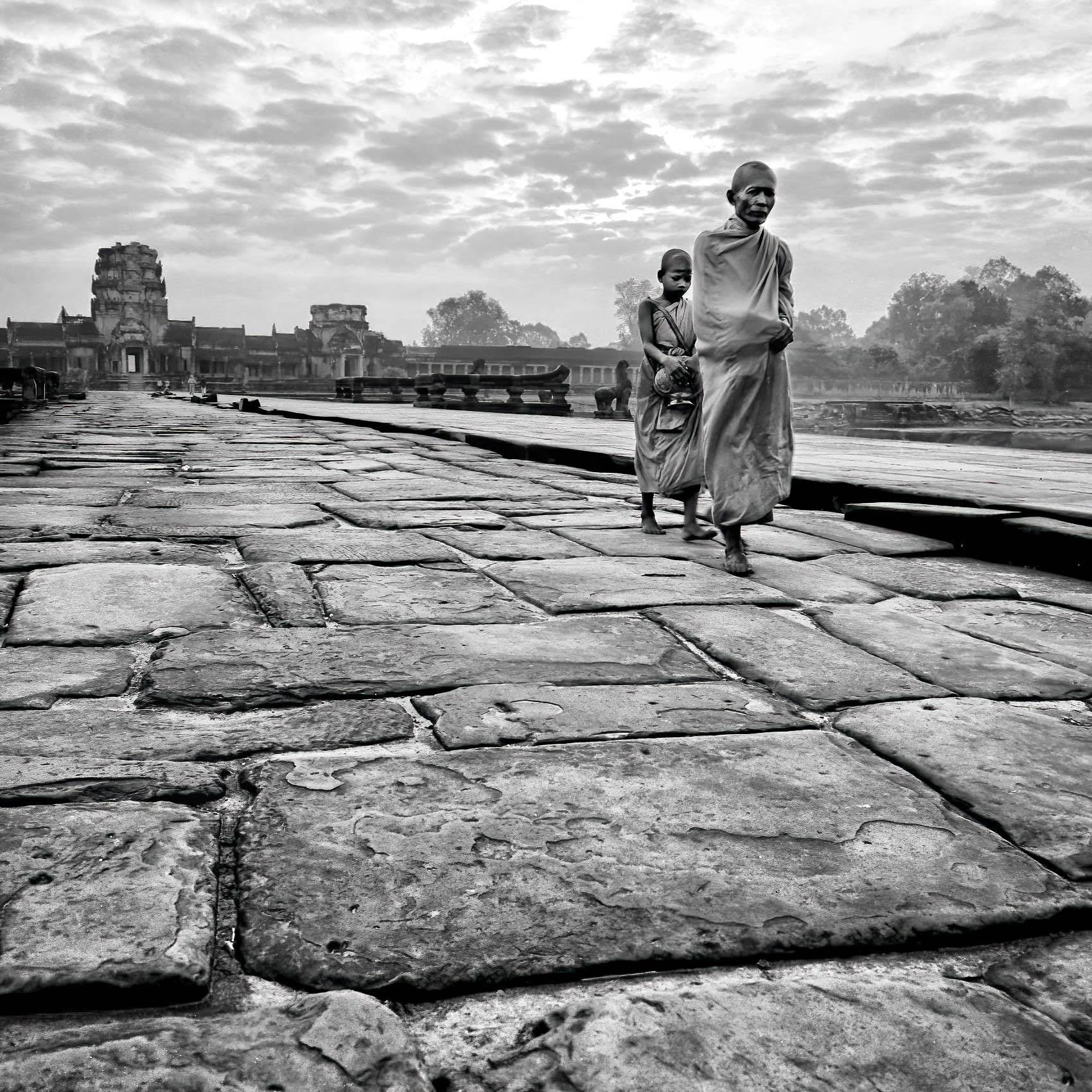 two-monks-walk-together-at-sunrise-in-angkor-wat-cambodia