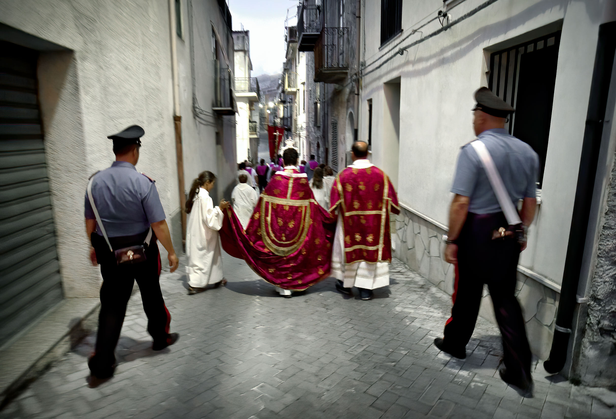 two policeman escort catholic priests during a religious festival in graterri sicily