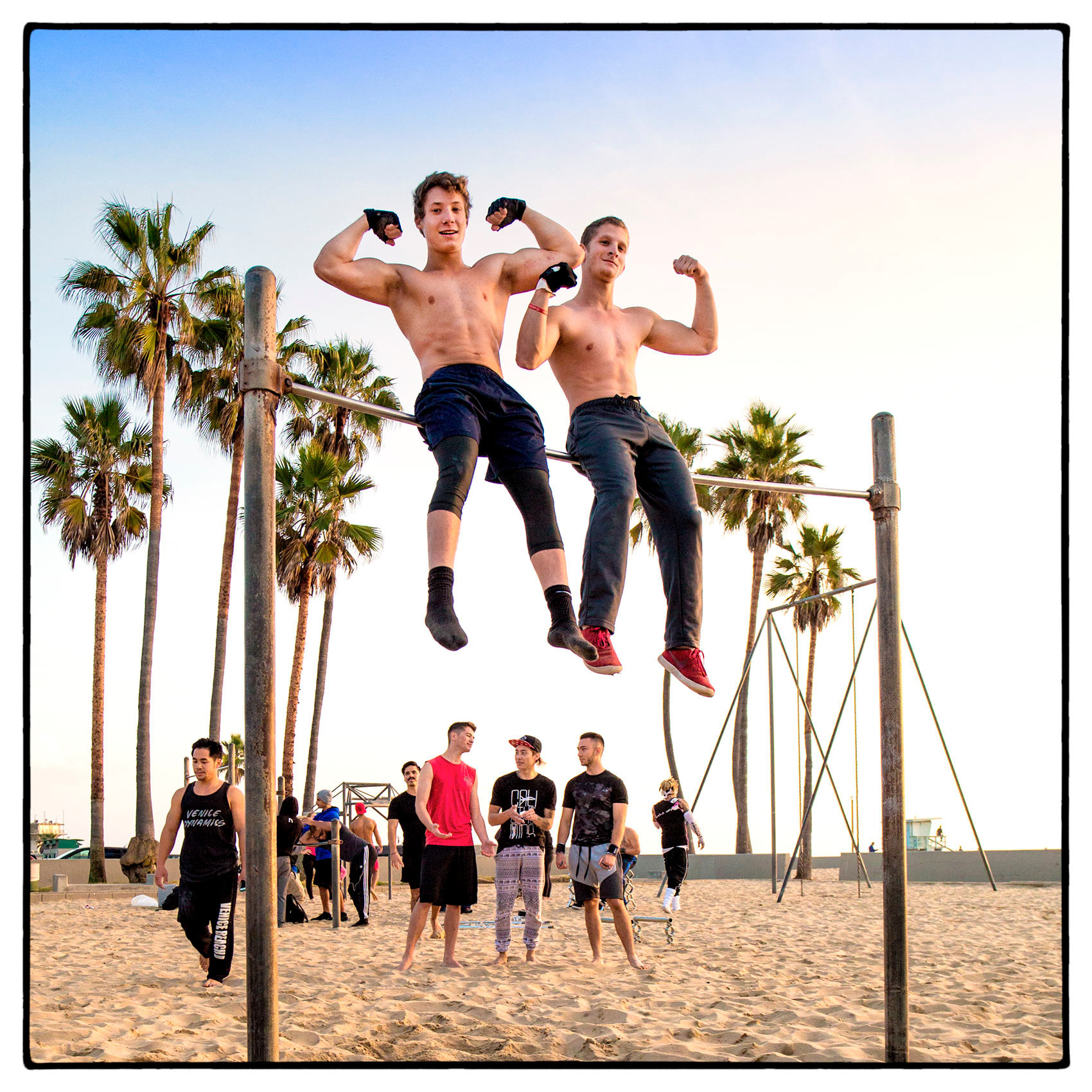 two-teenage-boys-show-off-their-muscles-while-sitting-on-a-parrallel-bar-in-venice-beach
