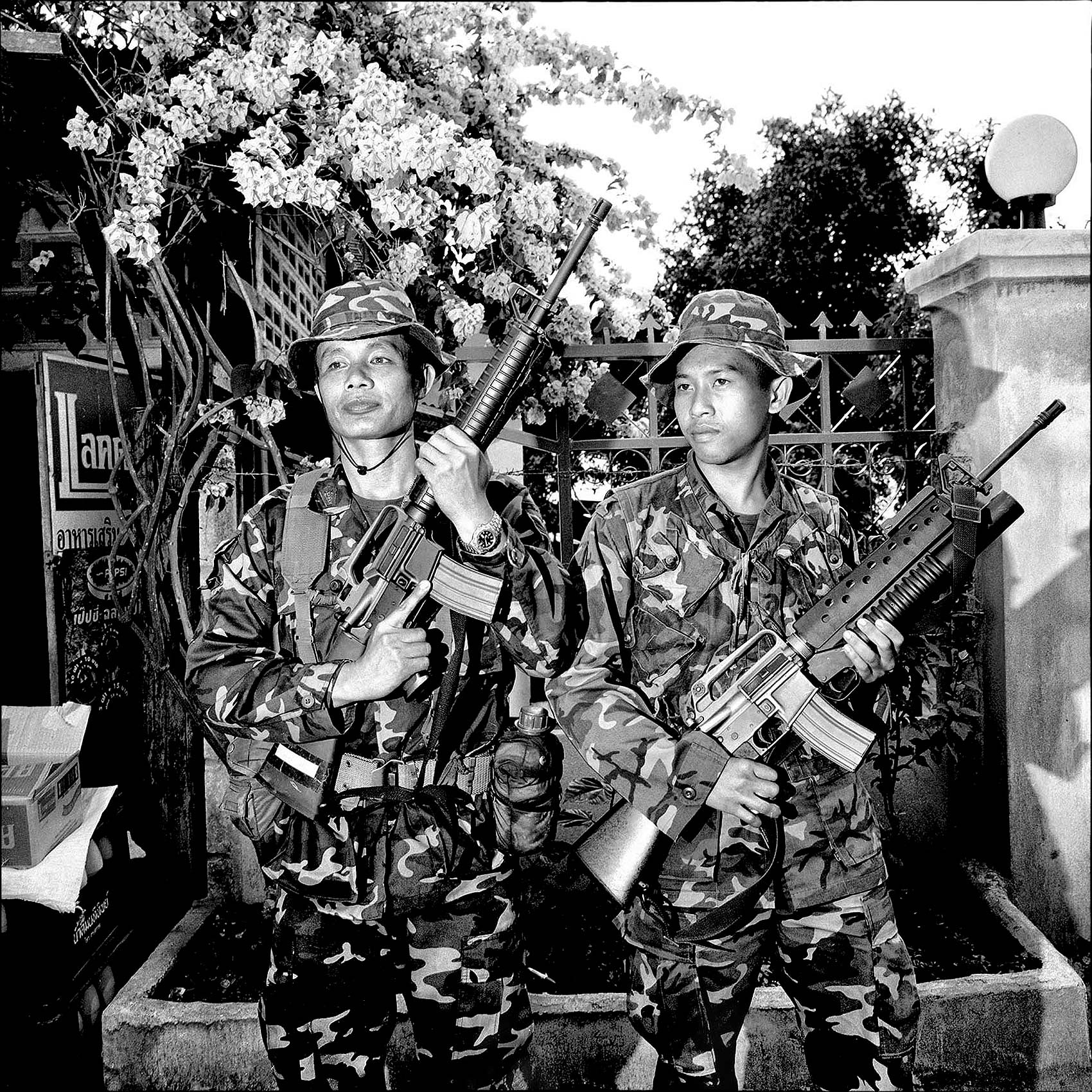 two-thai-soldiers-show-off-their-weapons-at-a-small-town-near-the-border-with-myanmar
